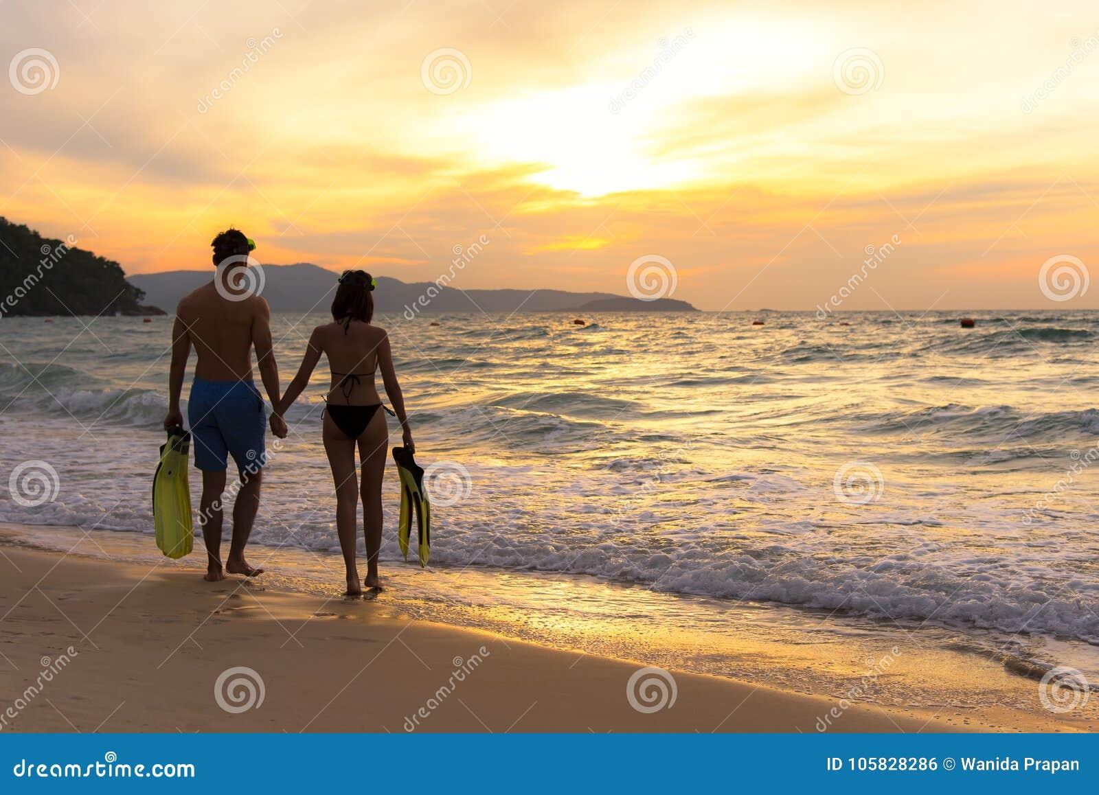 Vacaciones de verano Pares que caminan llevando a cabo las manos en tropical en el tiempo de la puesta del sol de la playa en día