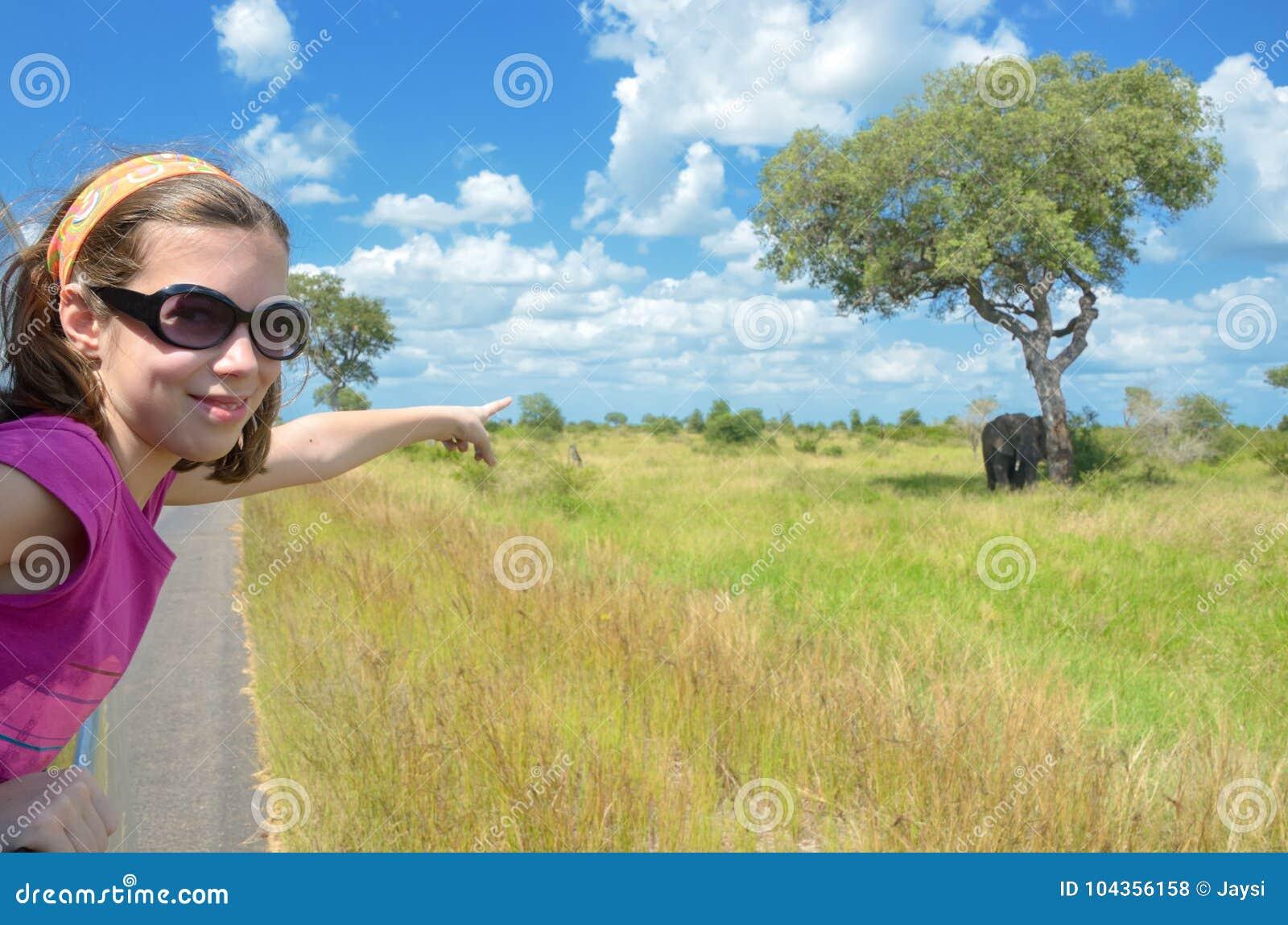 Vacaciones del safari de la familia en África, niño en elefante de observación del coche en la sabana africana, fauna del parque
