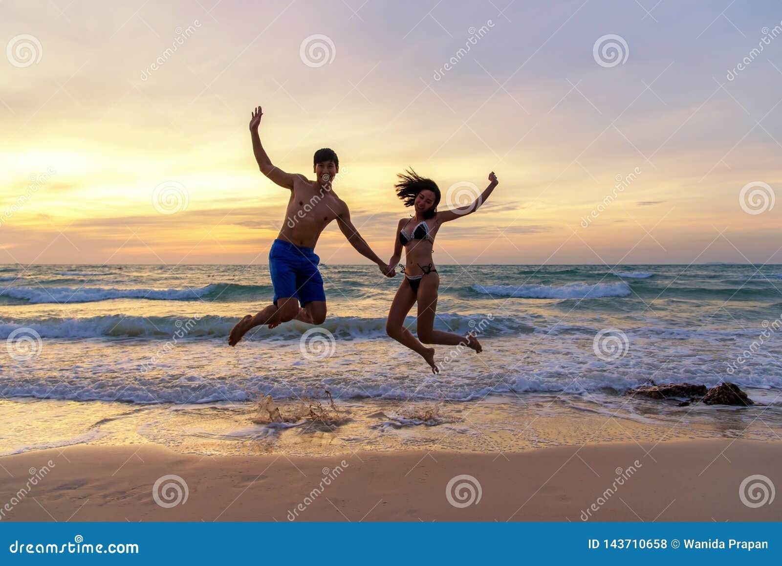 Vacances d été Couplez sauter en tenant des mains sur tropical le temps de coucher du soleil de plage dans des voyages de vacance