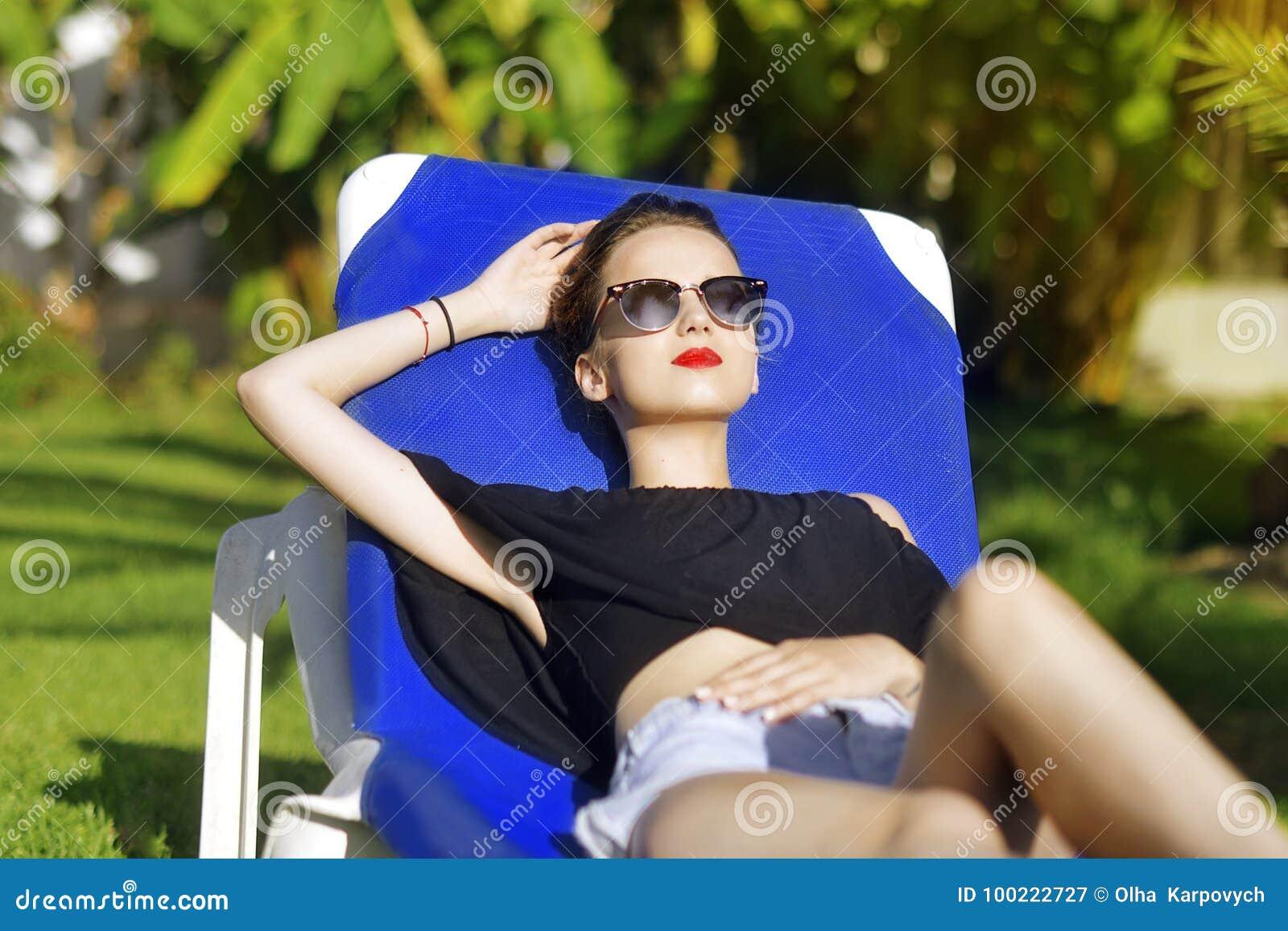 Vacances d été La fille de mode en verres de soleil détend À l arrière-plan un palmier Concept de vacances La belle fille se trou