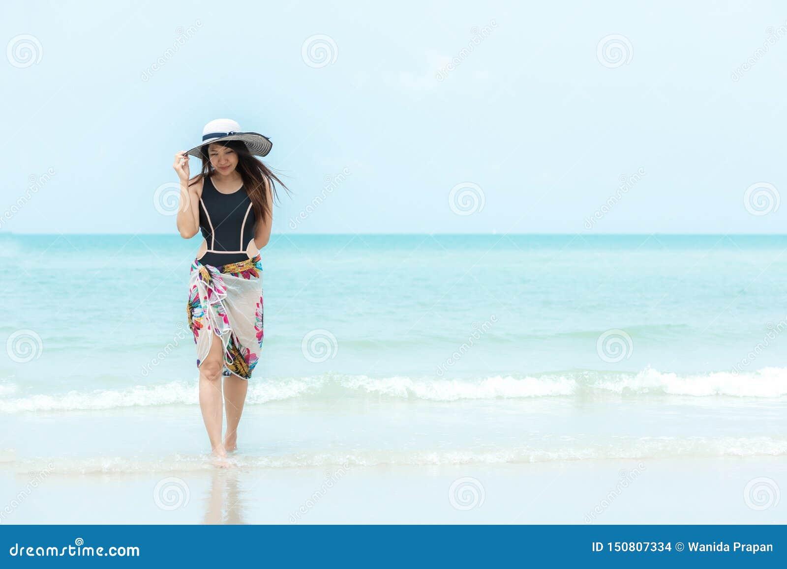 Vacances d ?t? Froid de femme de mode de vie tenant le grand chapeau blanc et portant des voyages d ?t? de mode de bikini marchan