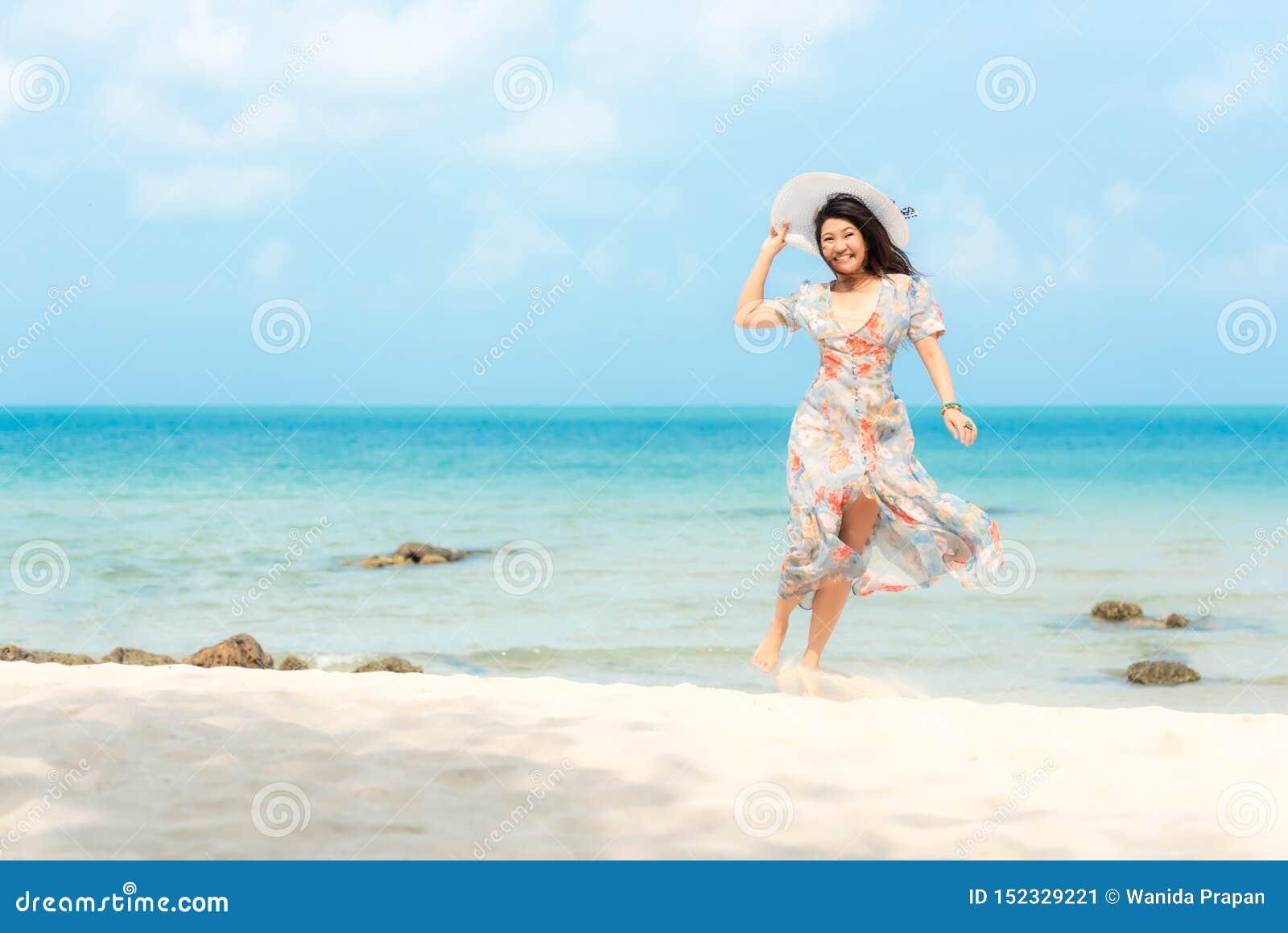 Vacances d ?t? Les voyages de port de sourire d été de mode de robe de femme asiatique de mode de vie détendent sur la plage arén