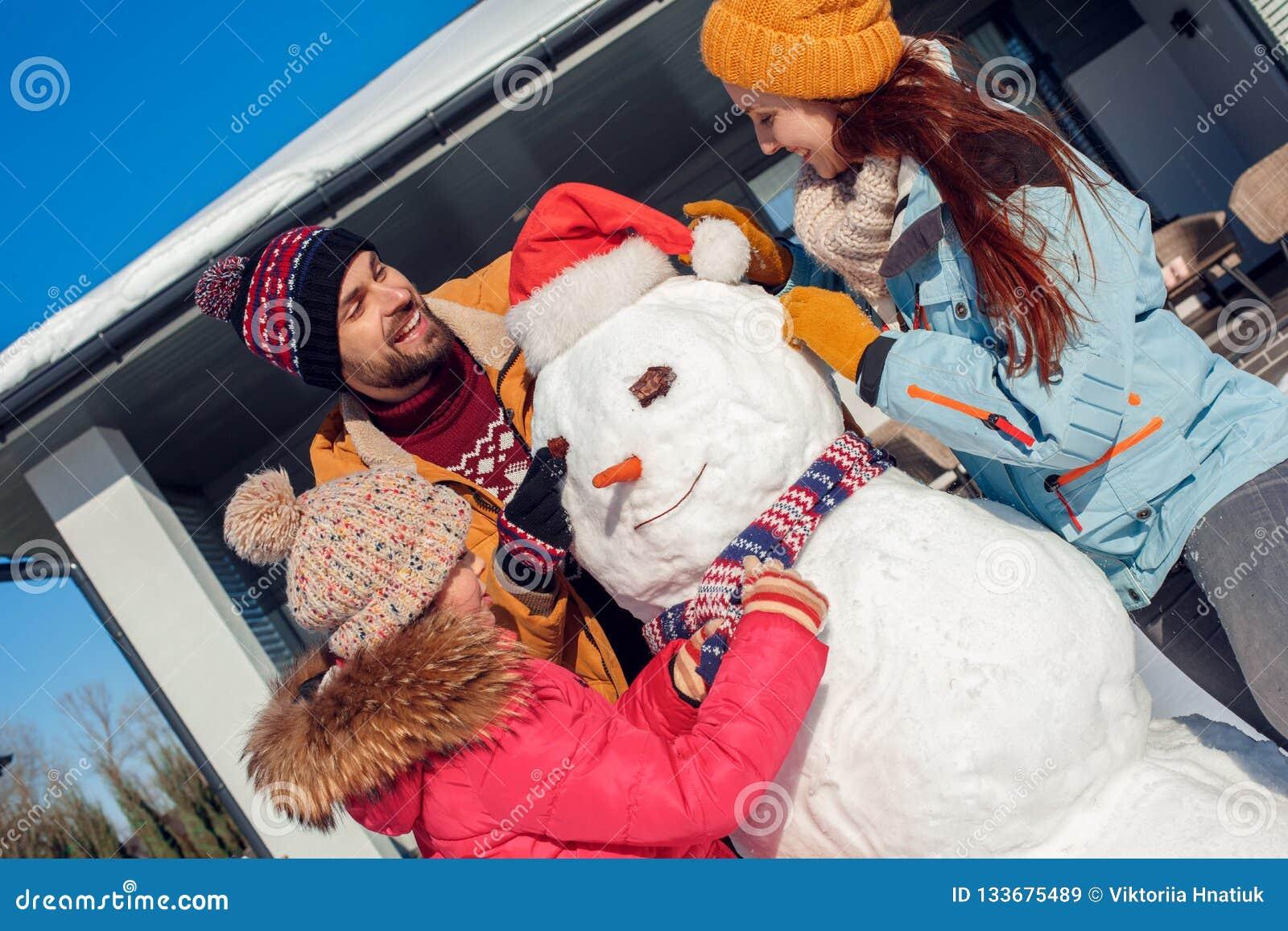 Vacances de l hiver Temps de famille se tenant ensemble dehors près de la maison rendant le sourire d écharpe de puttingon de fil