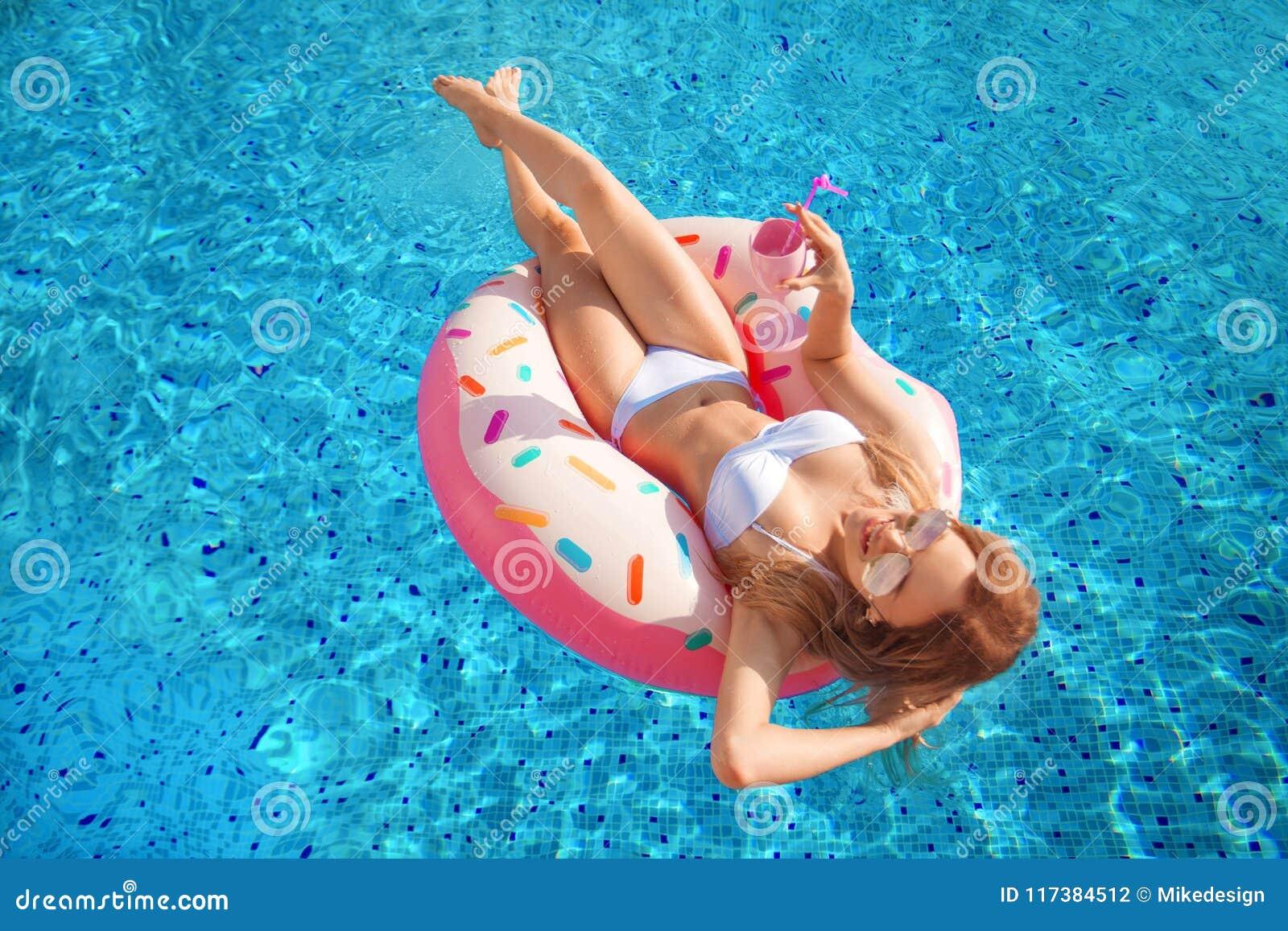 Vacanza di estate Donna in bikini sul materasso gonfiabile della ciambella nella piscina della STAZIONE TERMALE Viaggio al resto