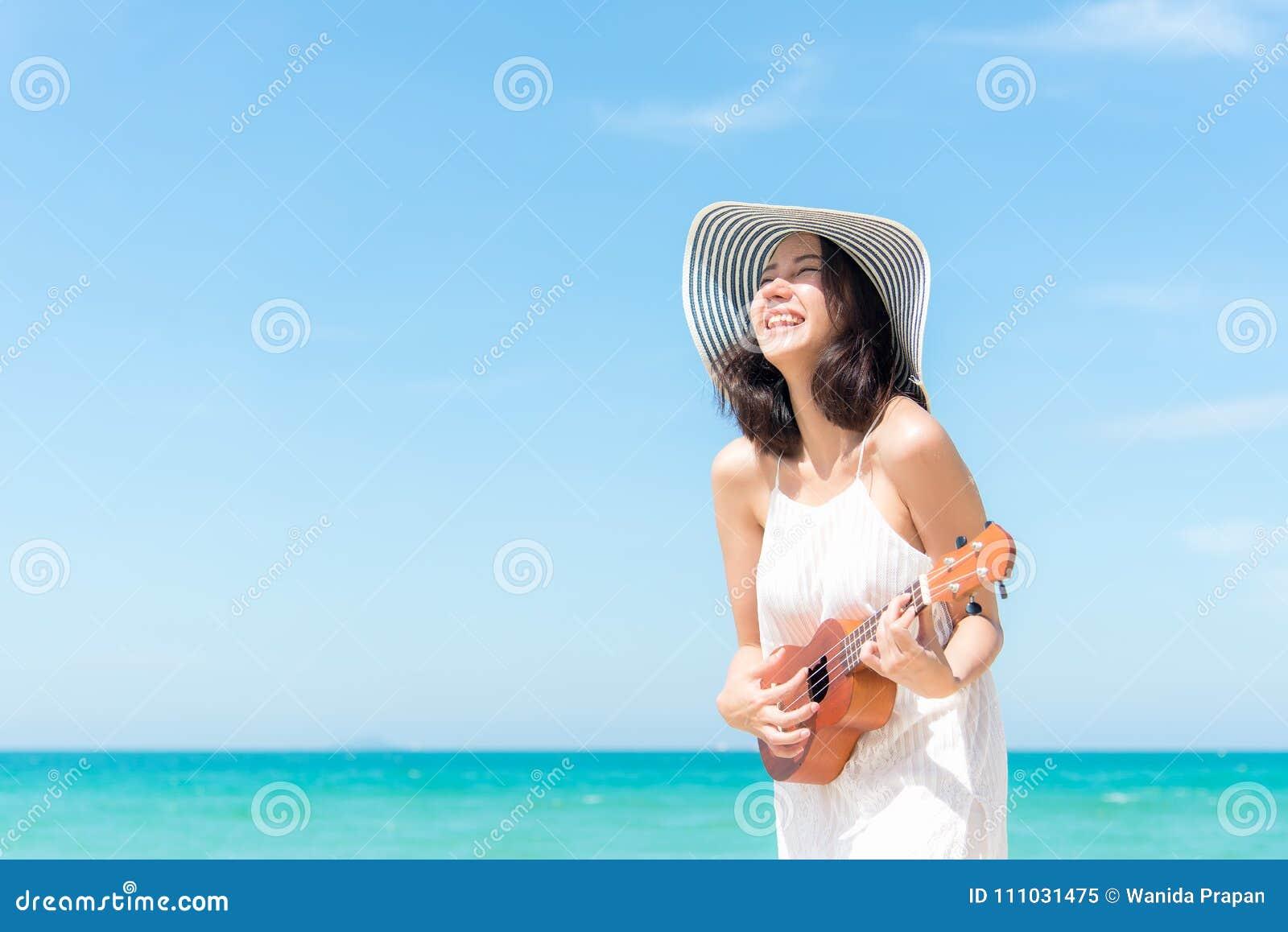 Vacanza di estate Donne asiatiche odoranti che si rilassano e che giocano le ukulele sulla spiaggia, così felice e di lusso di es