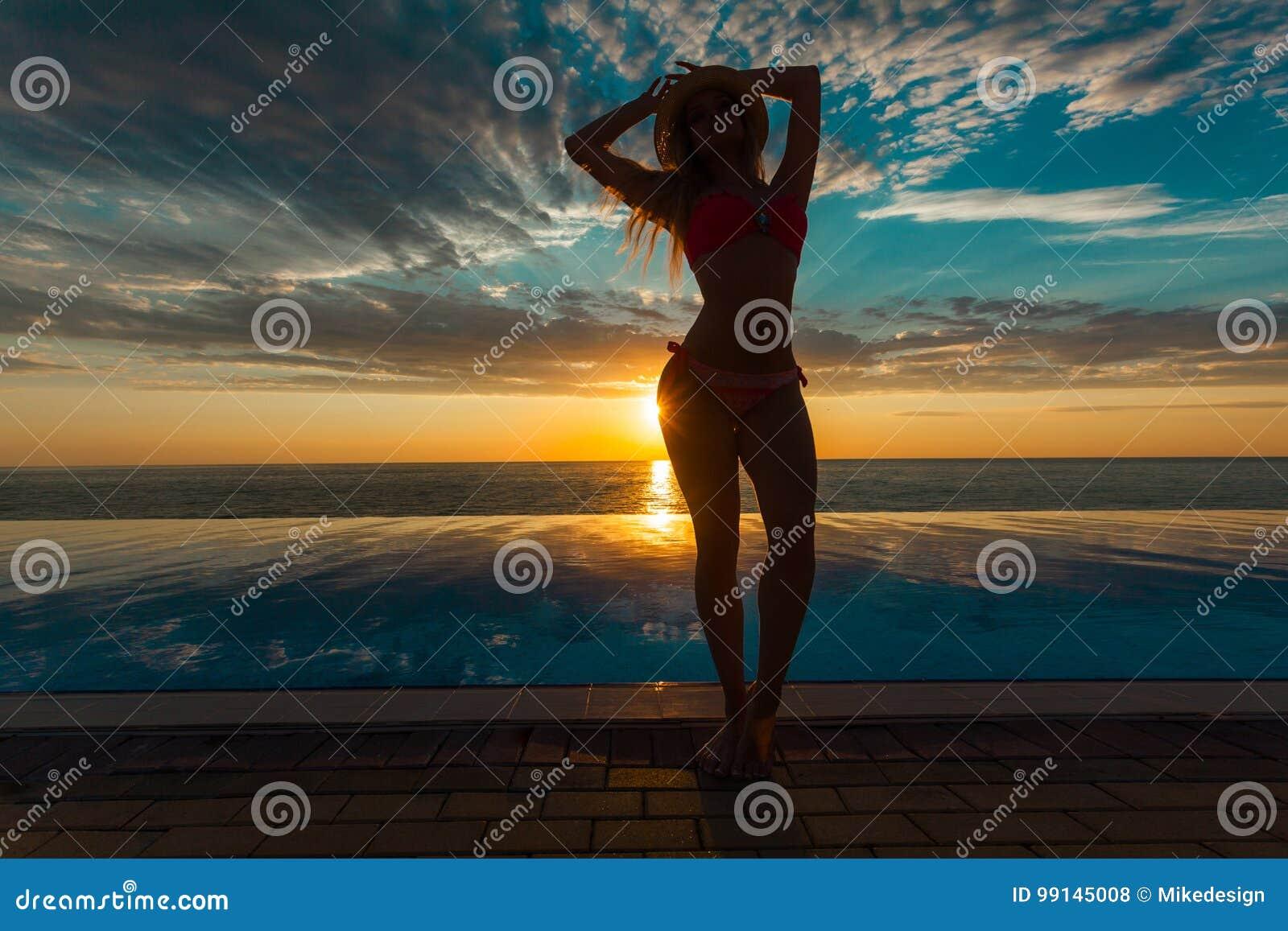 Vacanza di estate Siluetta della donna di dancing di bellezza sul tramonto vicino allo stagno con la vista di oceano