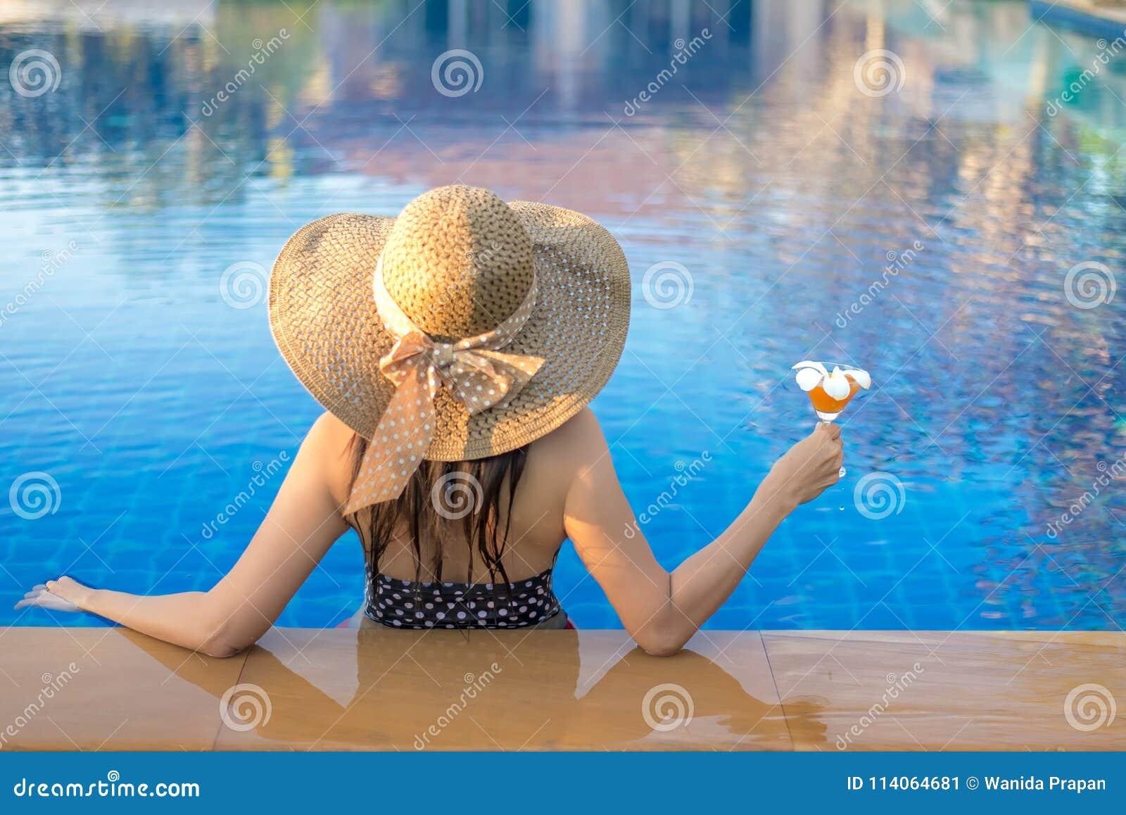 Vacanze di estate Donna di stile di vita soddisfatta del bikini e di grande cappello che si rilassano sulla piscina, nella festa