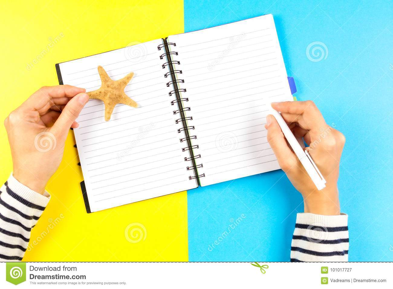 Vacation planning concept. Woman hand writing in open travel notebook over blue and yellow background.