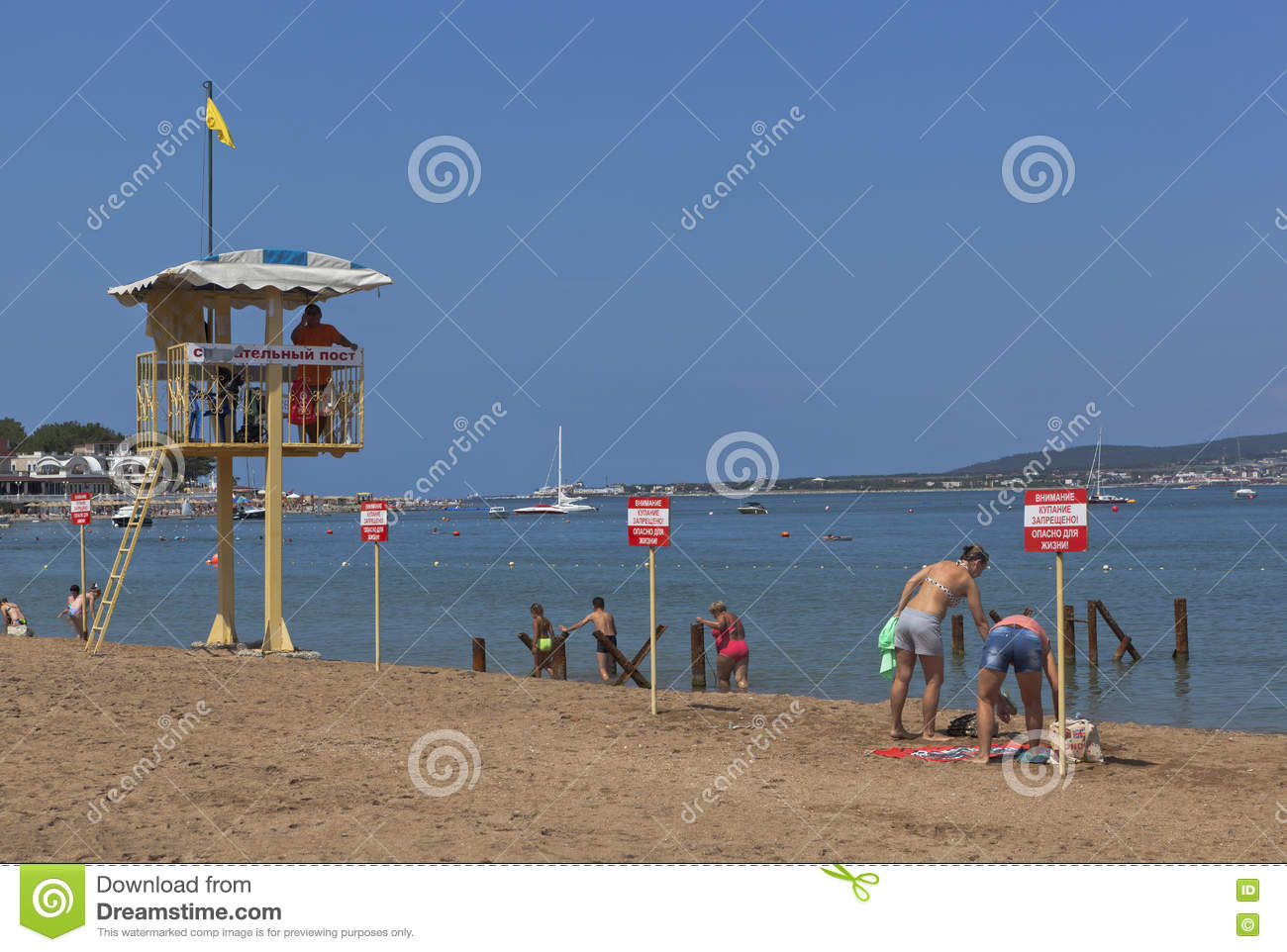 Vacationers people ignore the warning signs that says Warning! No swimming! Danger to life