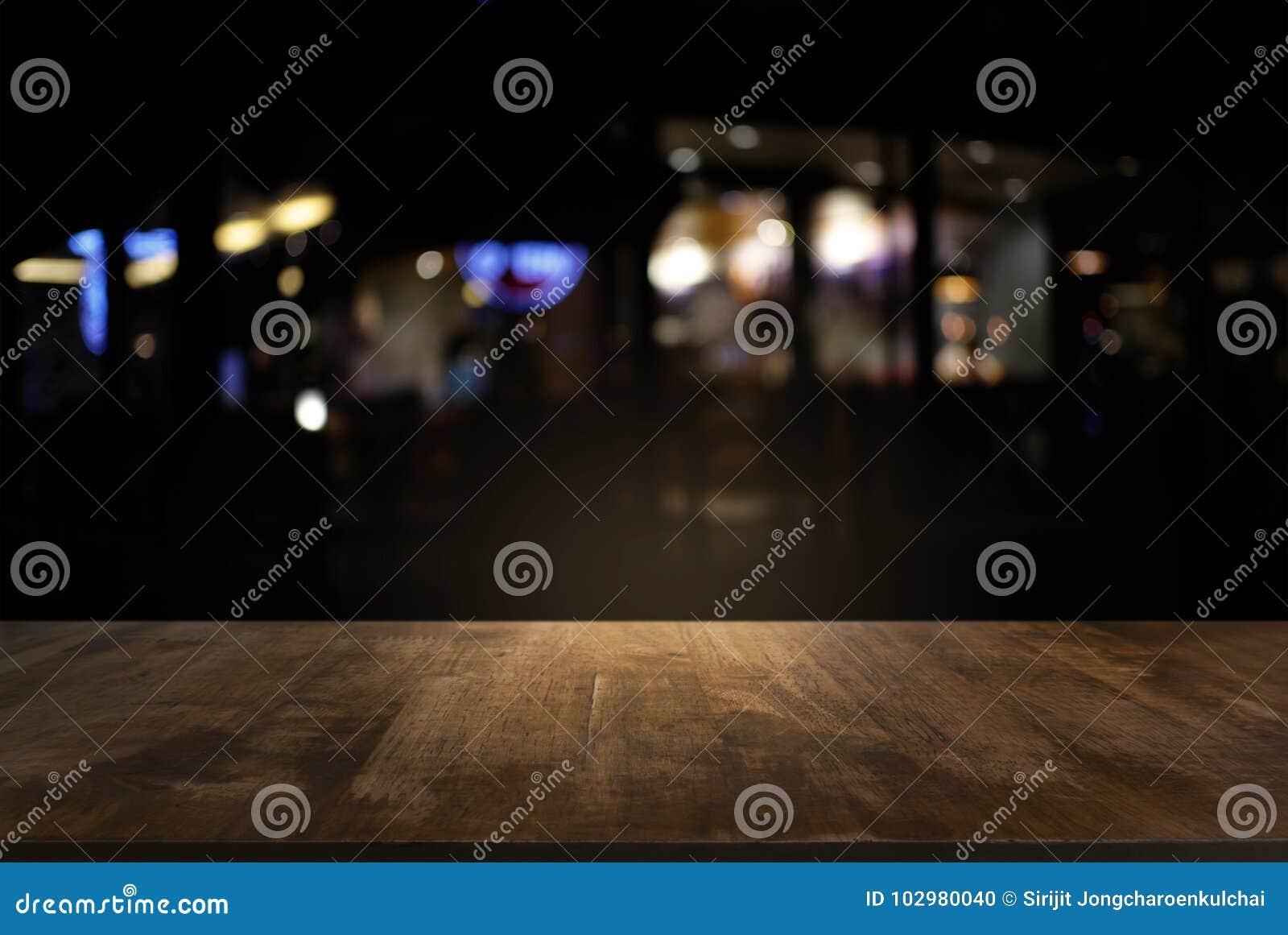 Vacie de la tabla de madera oscura delante del backgrou borroso extracto