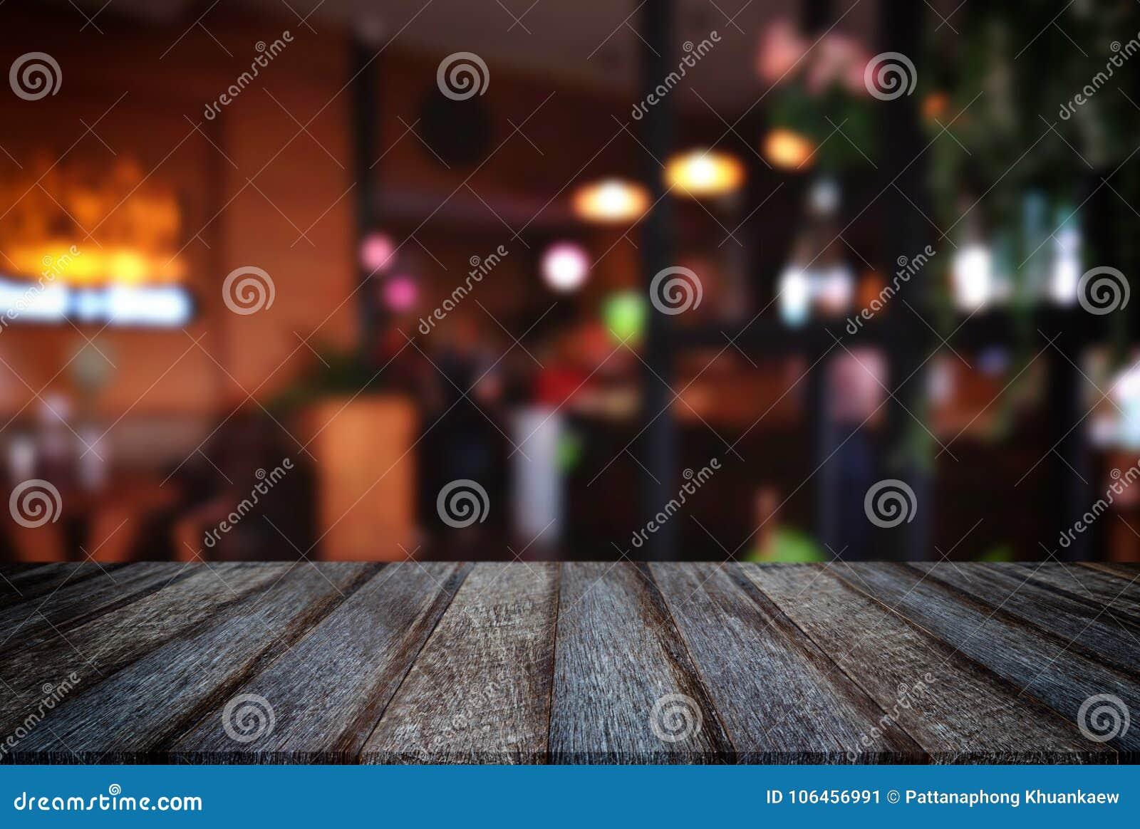 Vacie la tabla de madera y el fondo borroso del extracto en o delantero