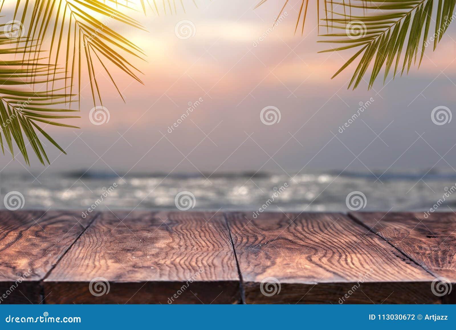 Vacie las hojas de madera de la tabla y de palma en un fondo de la playa borroso