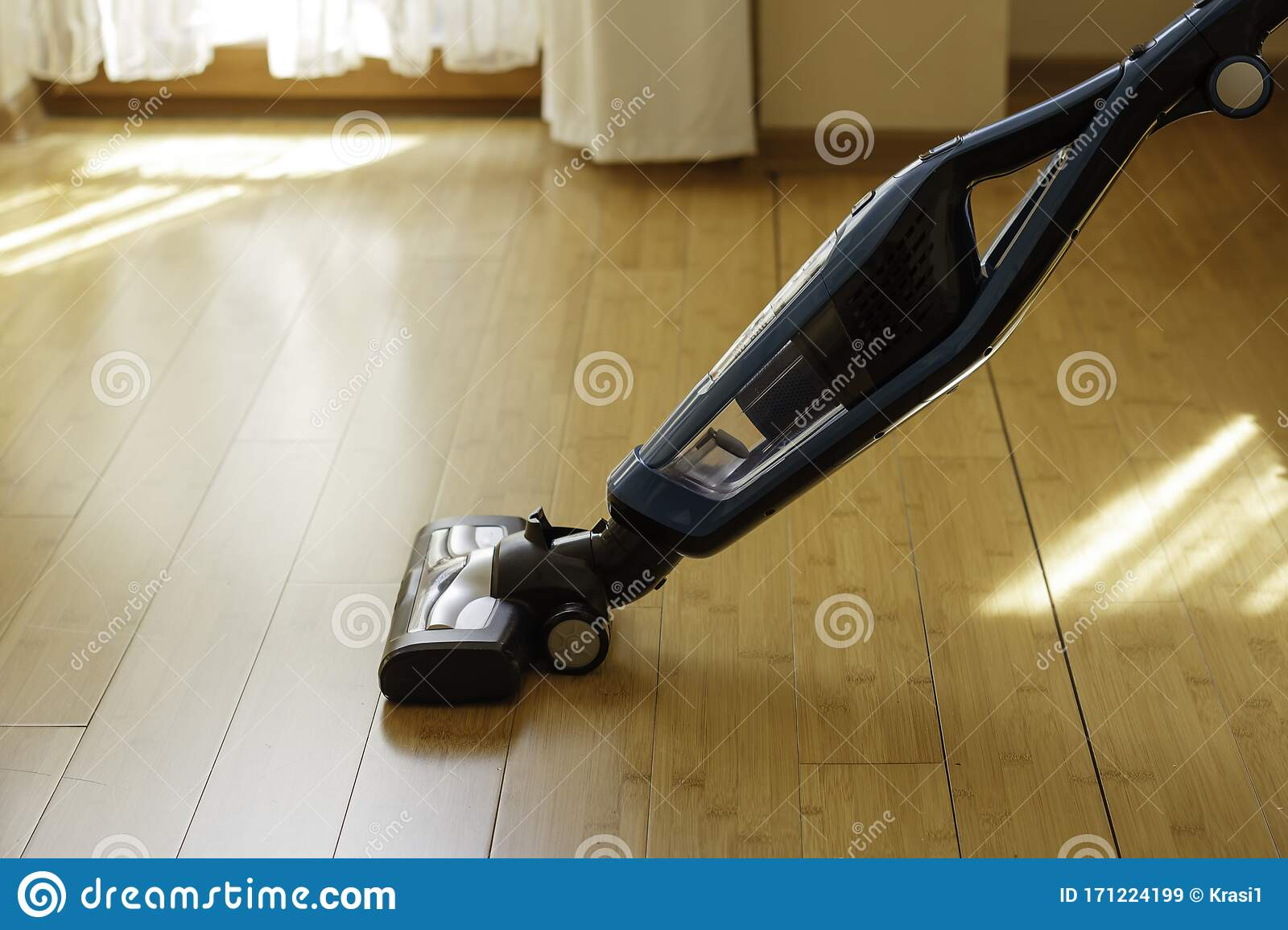 Vacuum Cleaner Cleaning Bamboo Flooring In A Room Stock Image