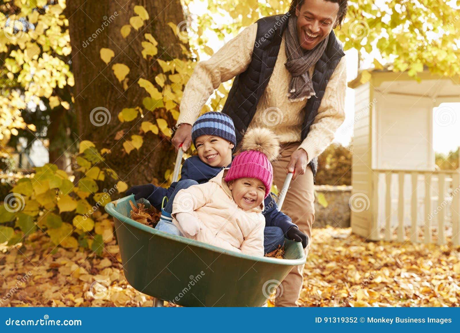Vader In Autumn Garden Gives Children Ride in Kruiwagen