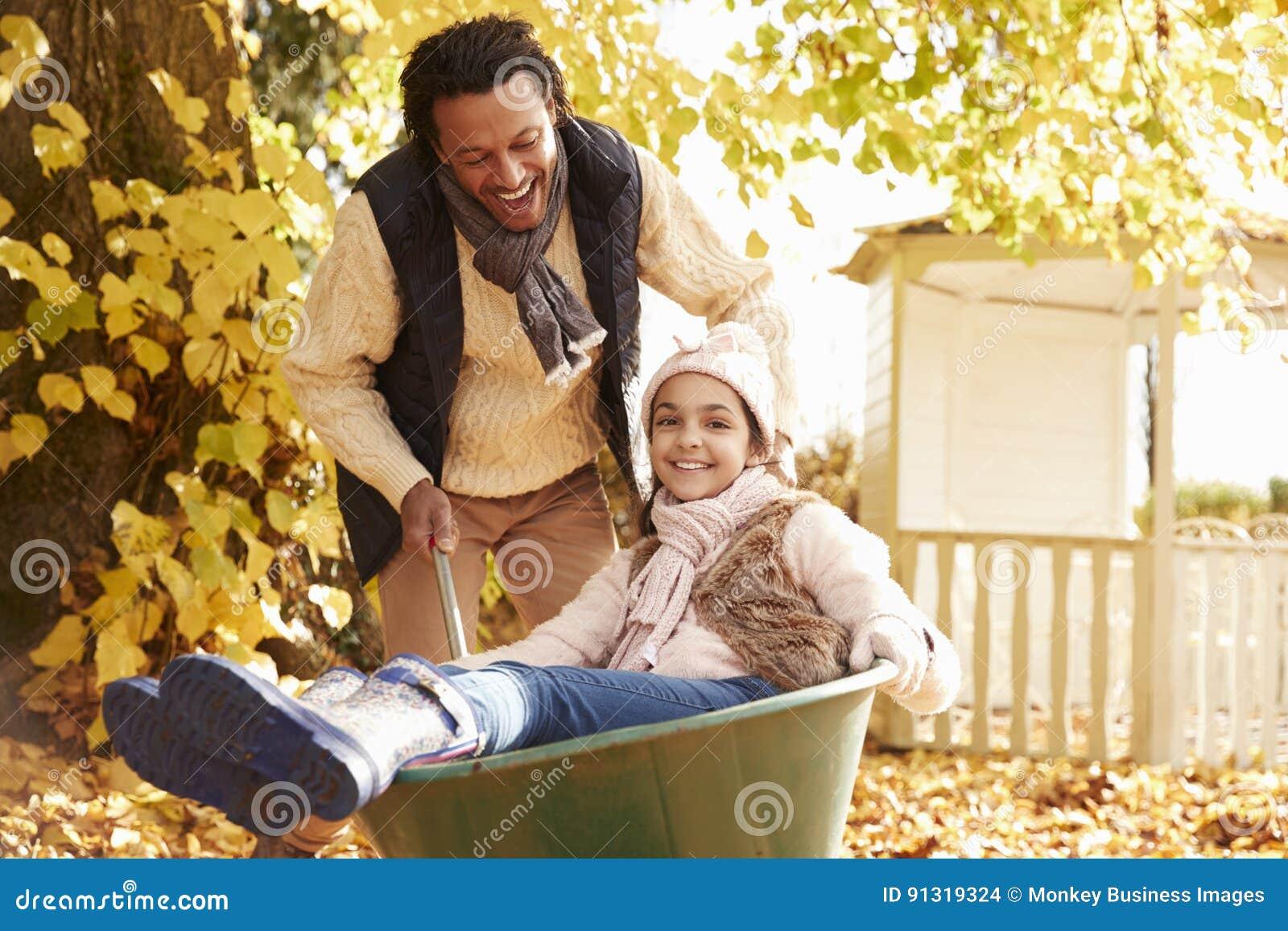 Vader In Autumn Garden Gives Daughter Ride in Kruiwagen