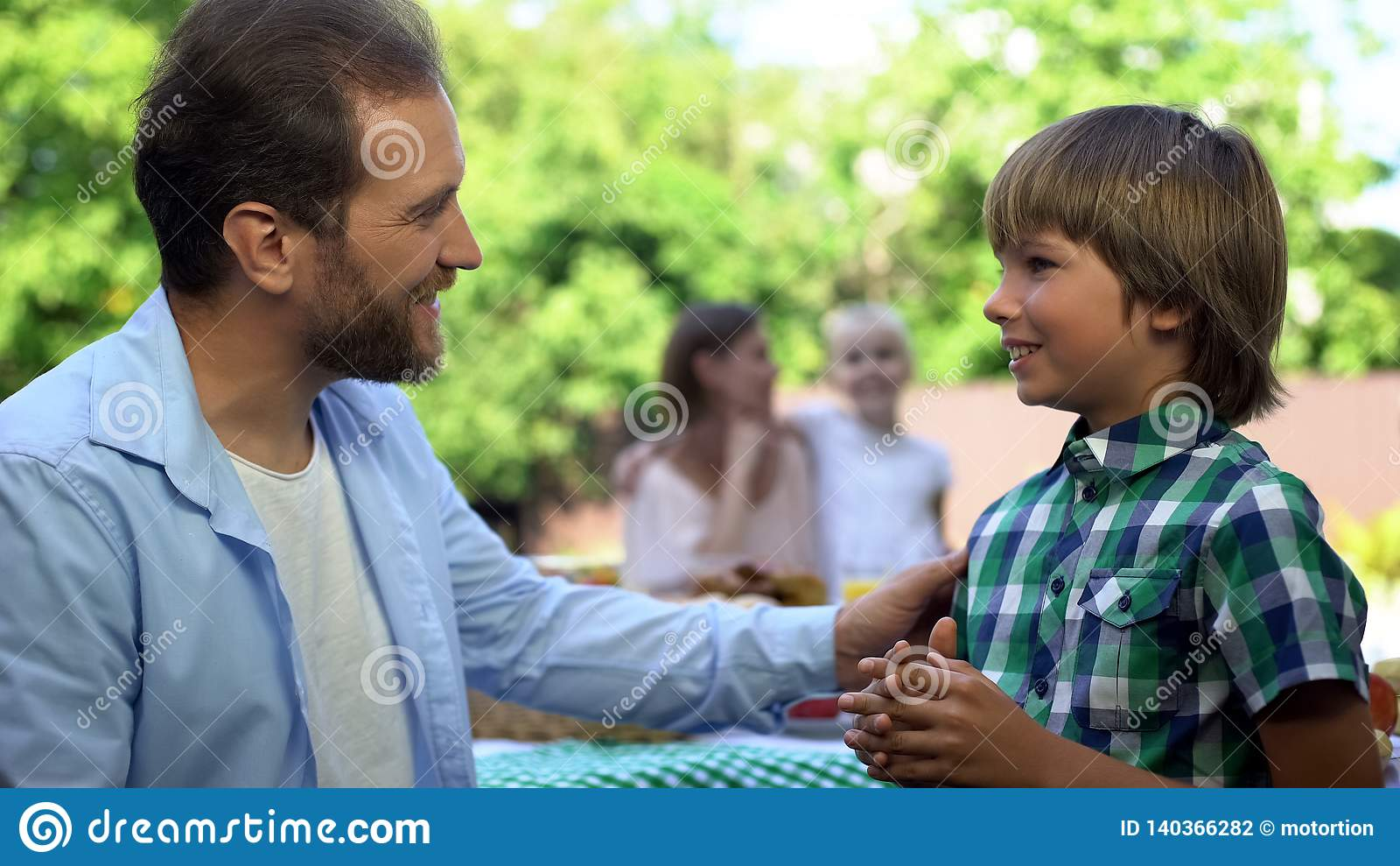 Vader die aan zoon, mamma spreekt dat met dochter op achtergrond, ouderschap spreekt