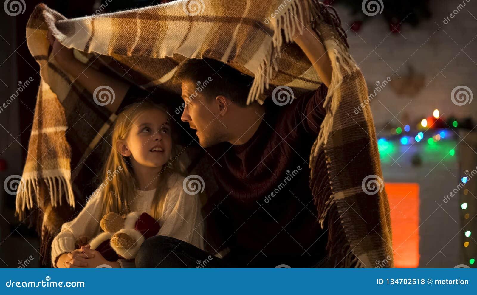 Vader die adembenemend Kerstmisverhaal voor meisjezitting vertellen onder comfortabele plaid