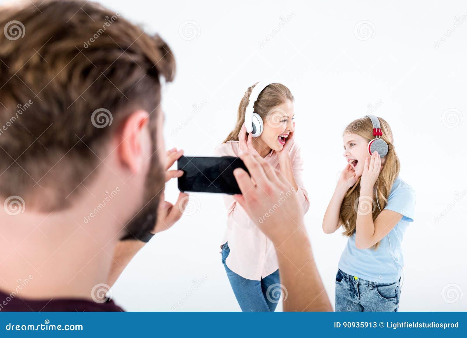 Vader die foto van moeder en dochter het luisteren muziek met hoofdtelefoons nemen en het zingen