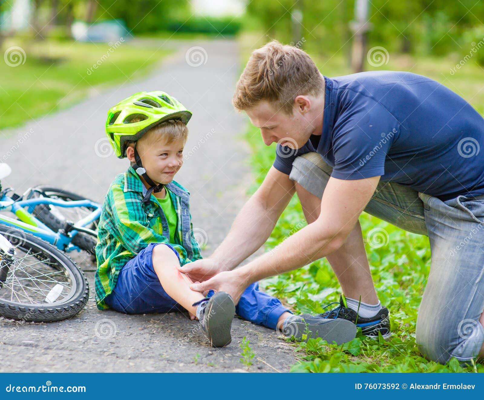 Vader die pleister op de verwonding van de jonge jongen zetten die van zijn b viel stock foto - Turquoise ruimte van de jongen ...