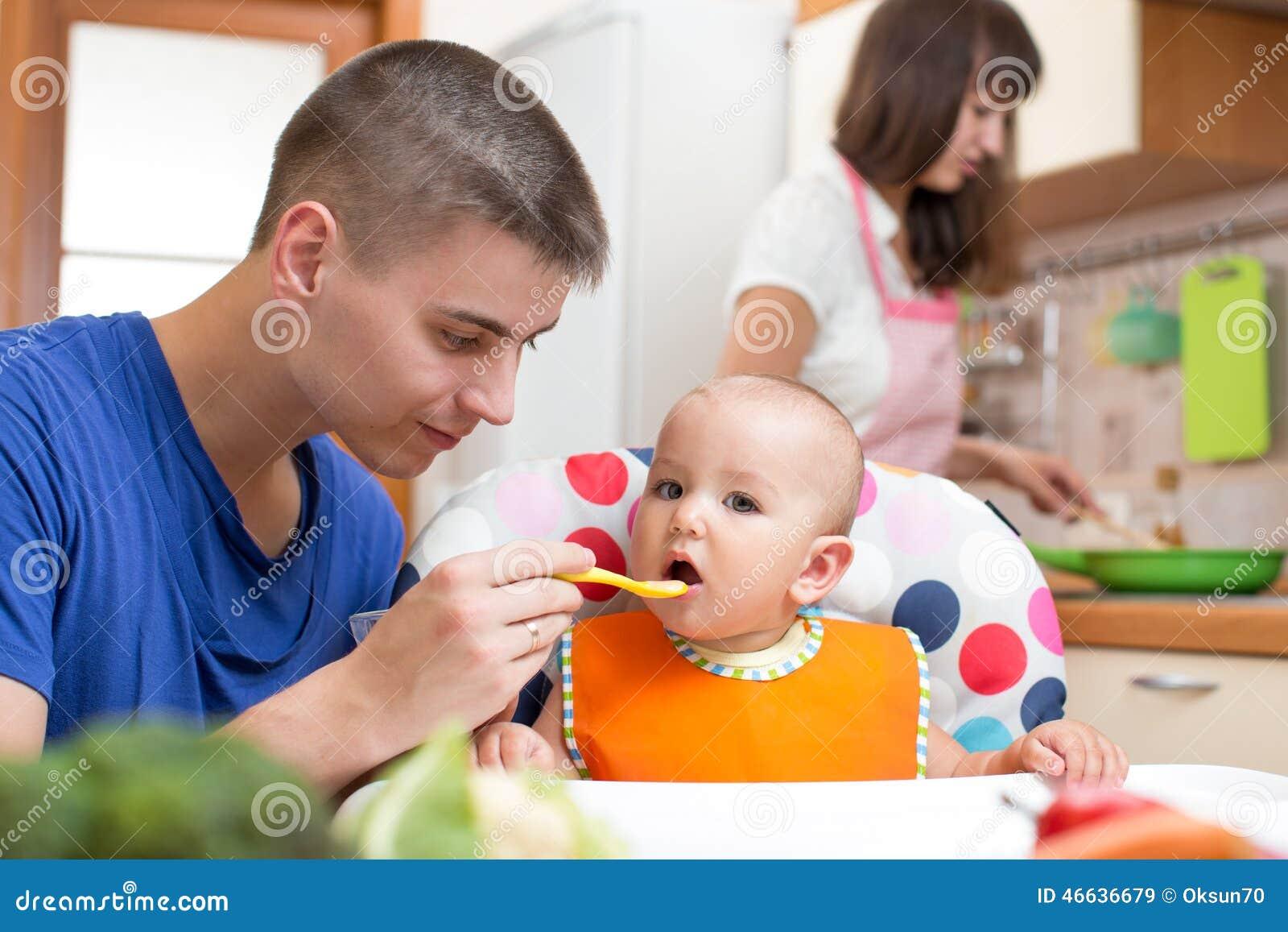 Vader die zijn baby en moeder het koken voeden bij
