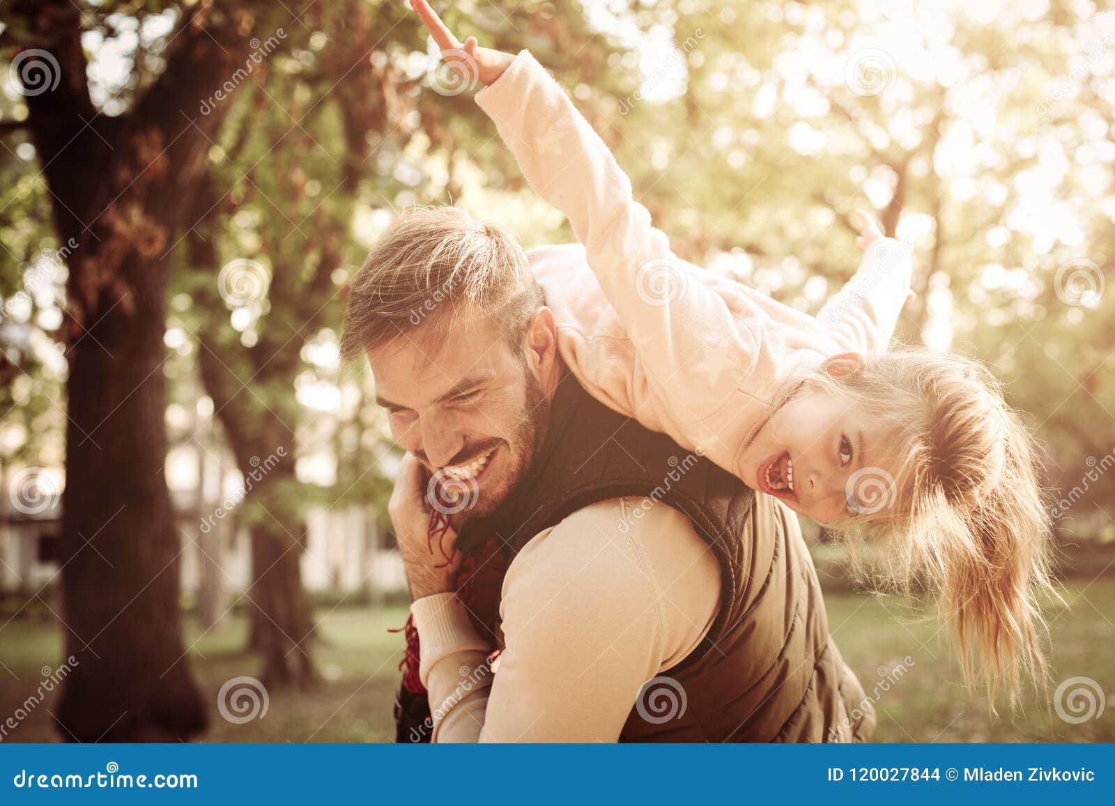 Vader die zijn dochter op schouders houden en spelen aan