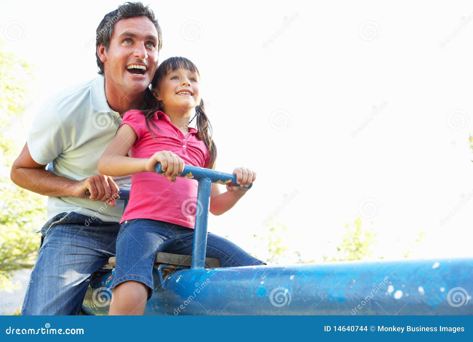 Vader en de Dochter die de berijden op zien Zaag in Playgroun