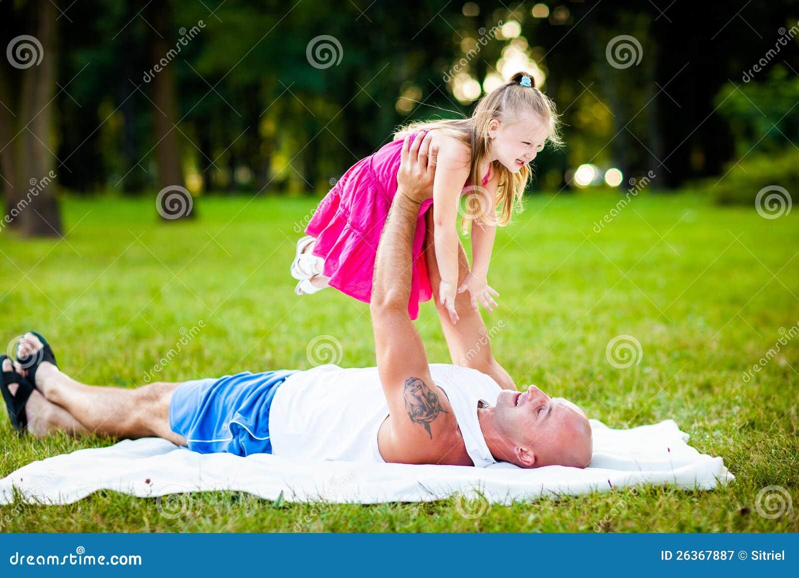 Vader en dochter die pret in een park hebben