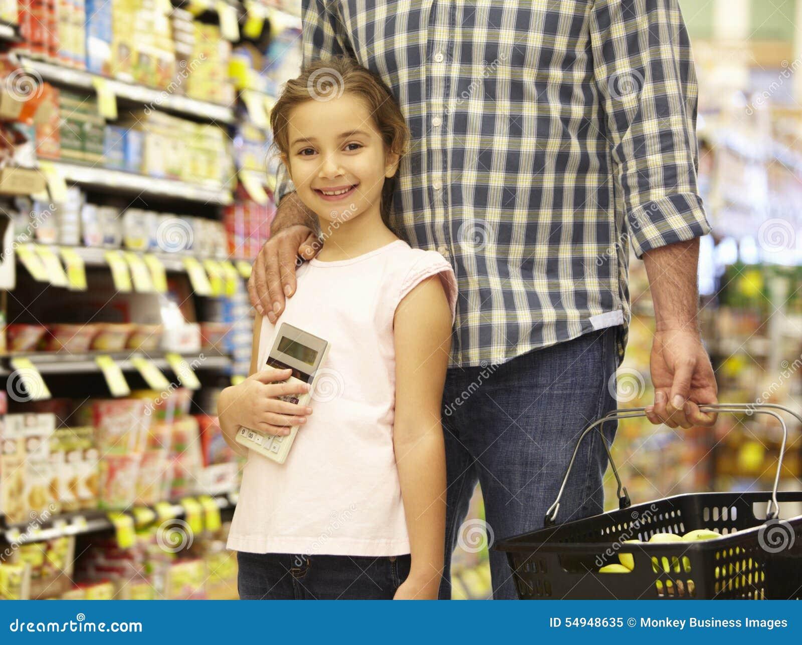 Vader en dochter die in supermarkt winkelen