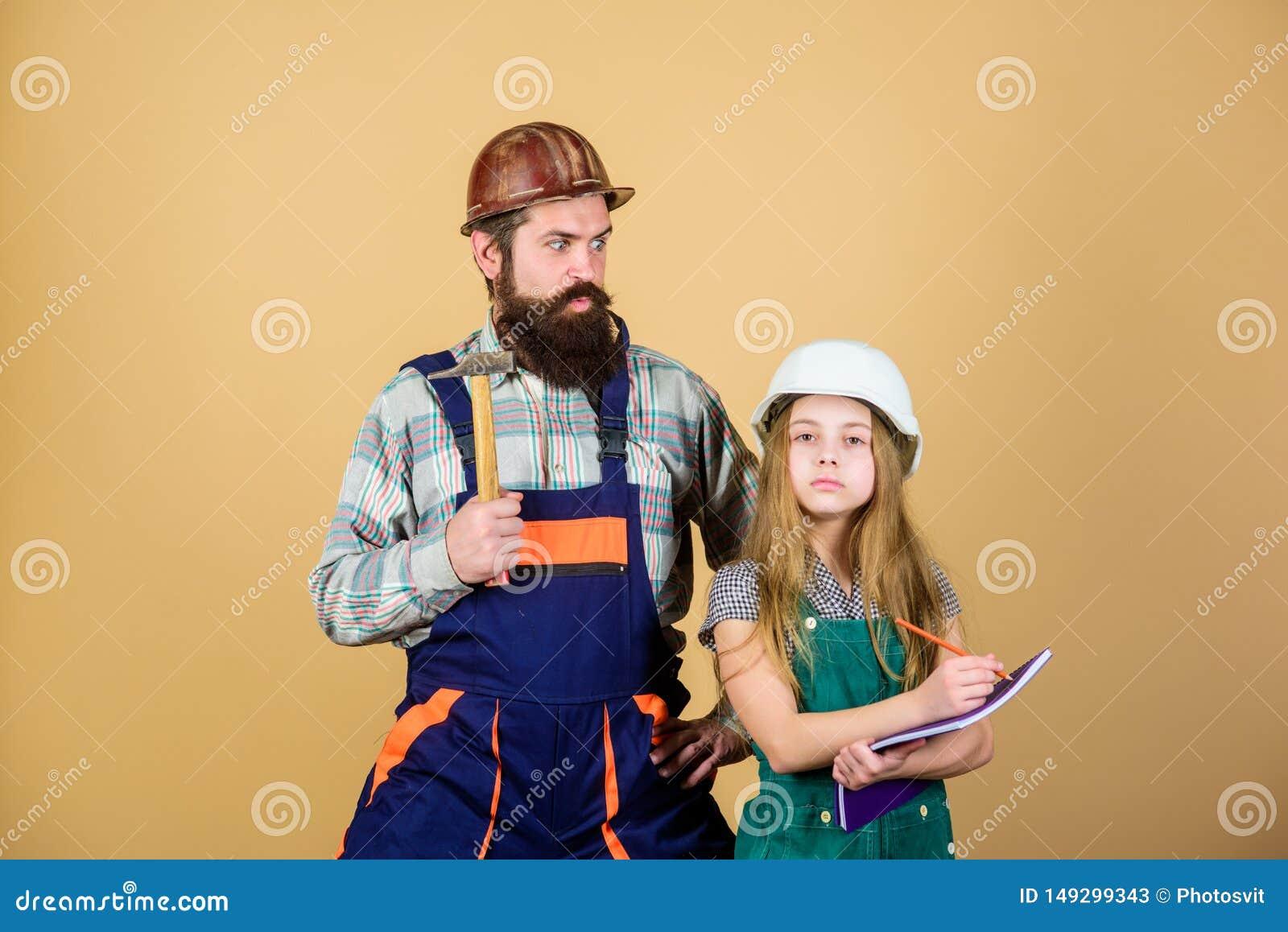 Vader en dochterbouwvakkerhelm eenvormig het vernieuwen huis Het huisverbetering activiteit Jong geitjemeisje planningsvernieuwin