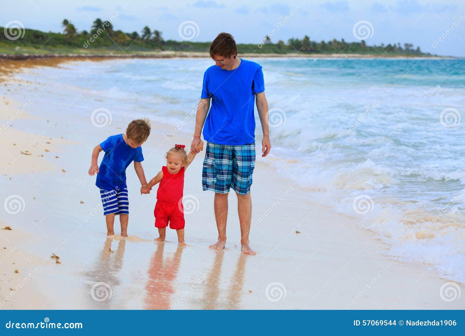 Vader en twee jonge geitjes die op het strand lopen
