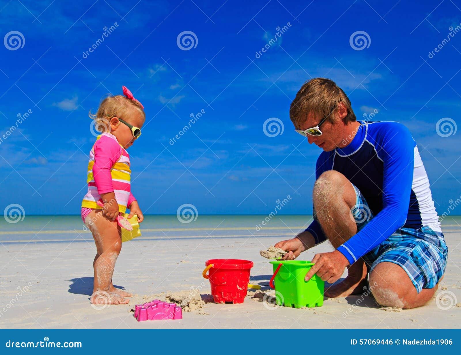 Vader en weinig dochter die met zand spelen