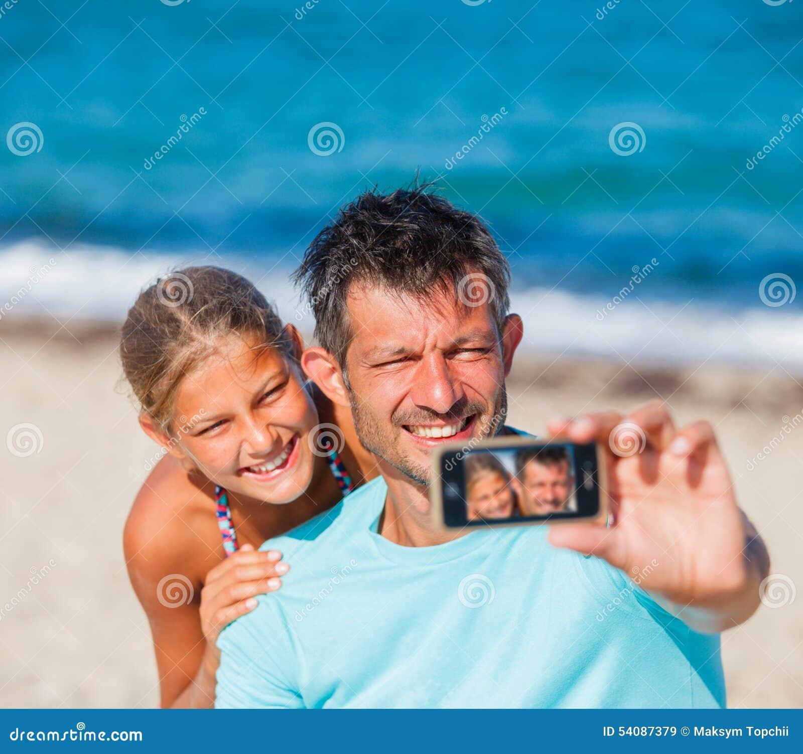 Vader en zijn jonge geitjes bij strand die selfie nemen