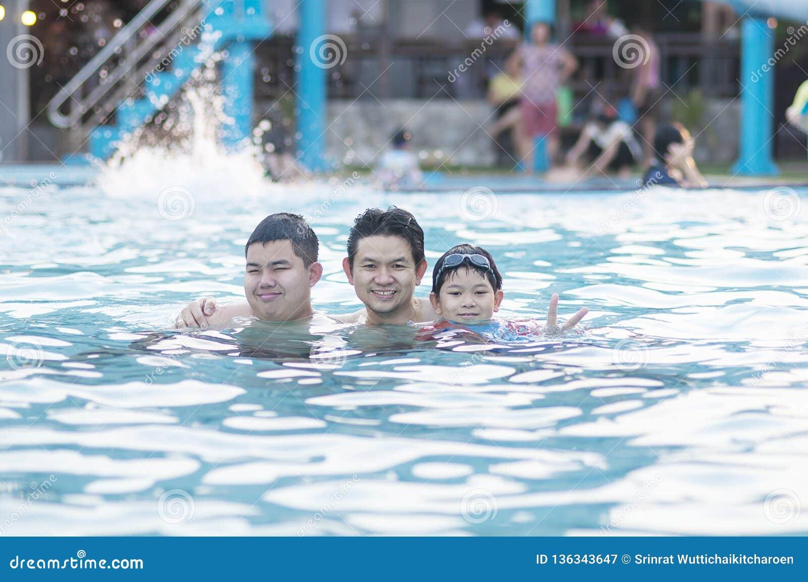 Vader en zijn twee zoonsspel in duidelijk water
