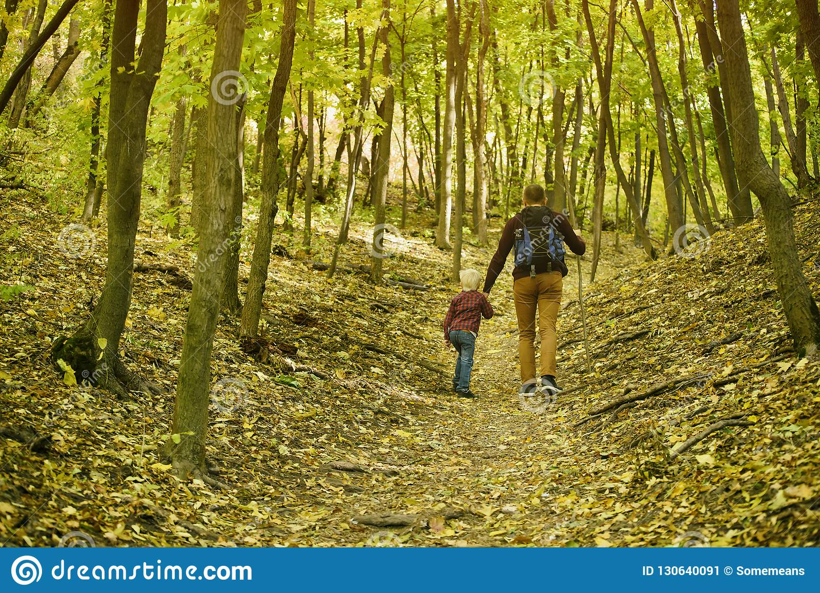 Vader en zoon die in de de herfst bos Achtermening lopen