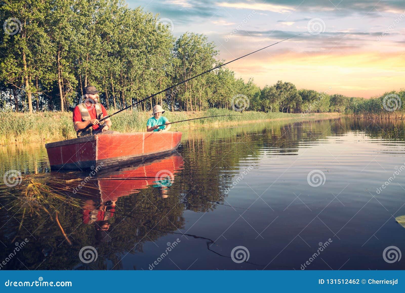 Vader en zoon die met hengels in een houten boot vissen