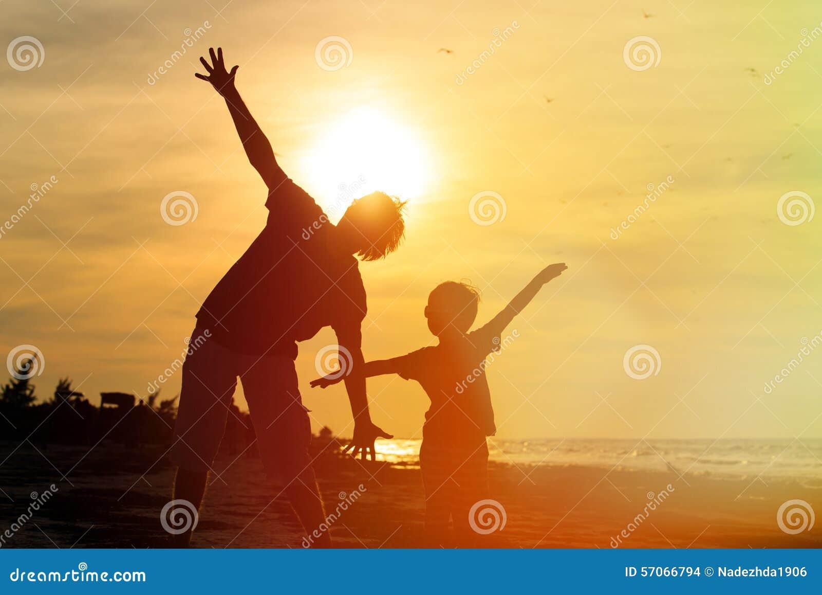 Vader en zoon die pret op zonsondergang hebben
