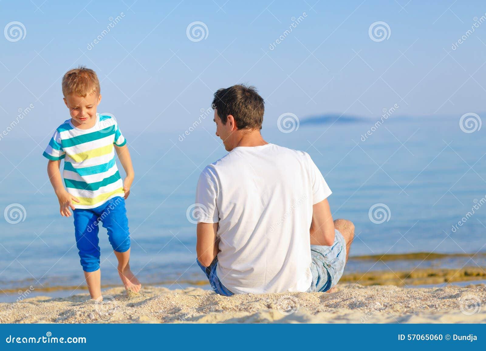 Vader en zoon die van tijd genieten bij het strand
