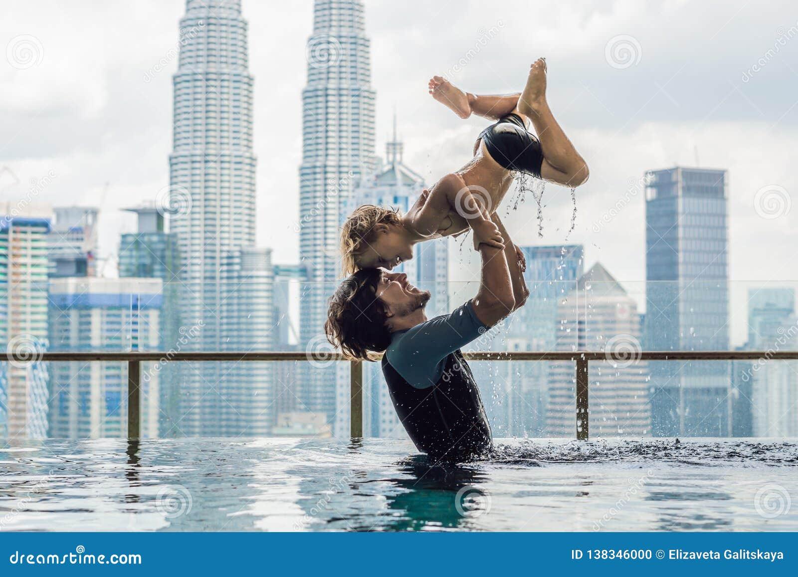 Vader en zoon in openlucht zwembad met stadsmening in blauwe hemel