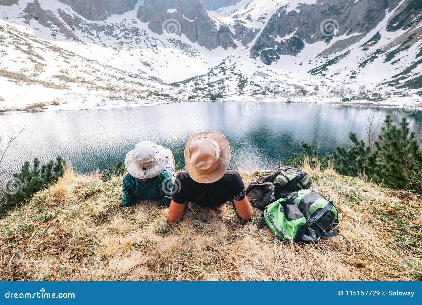 Vader en zoons de backpackersrust dichtbij het bergmeer en geniet van