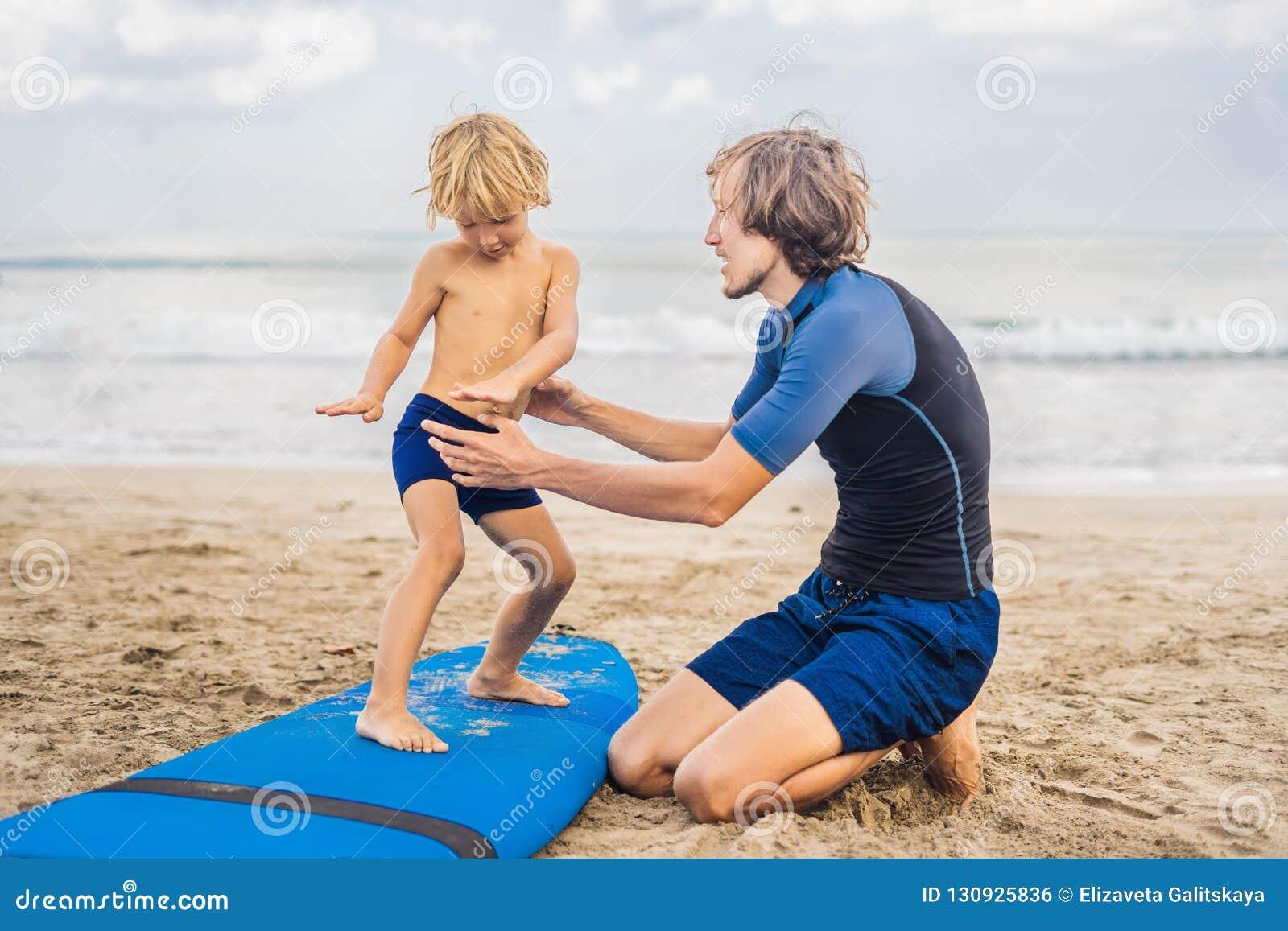 Vader of instructeur die zijn 4 éénjarigenzoon onderwijzen hoe te binnen te surfen