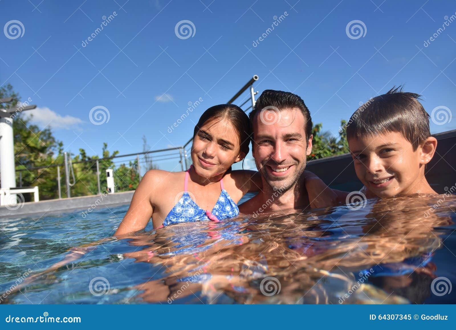 Vader met kinderen die pret in zwembad hebben