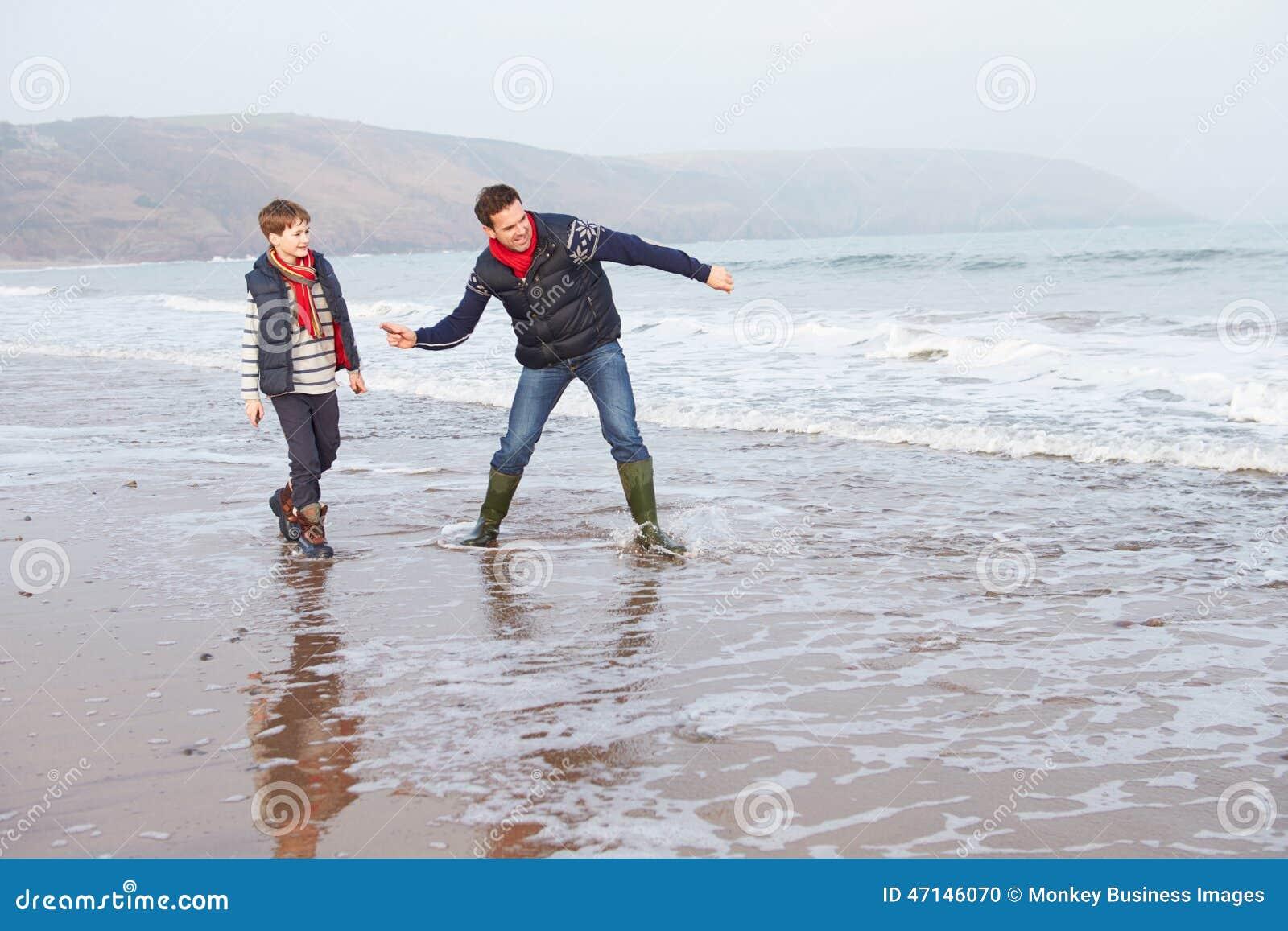 Vader And Son Walking op de Winterstrand en het Werpen van Stenen