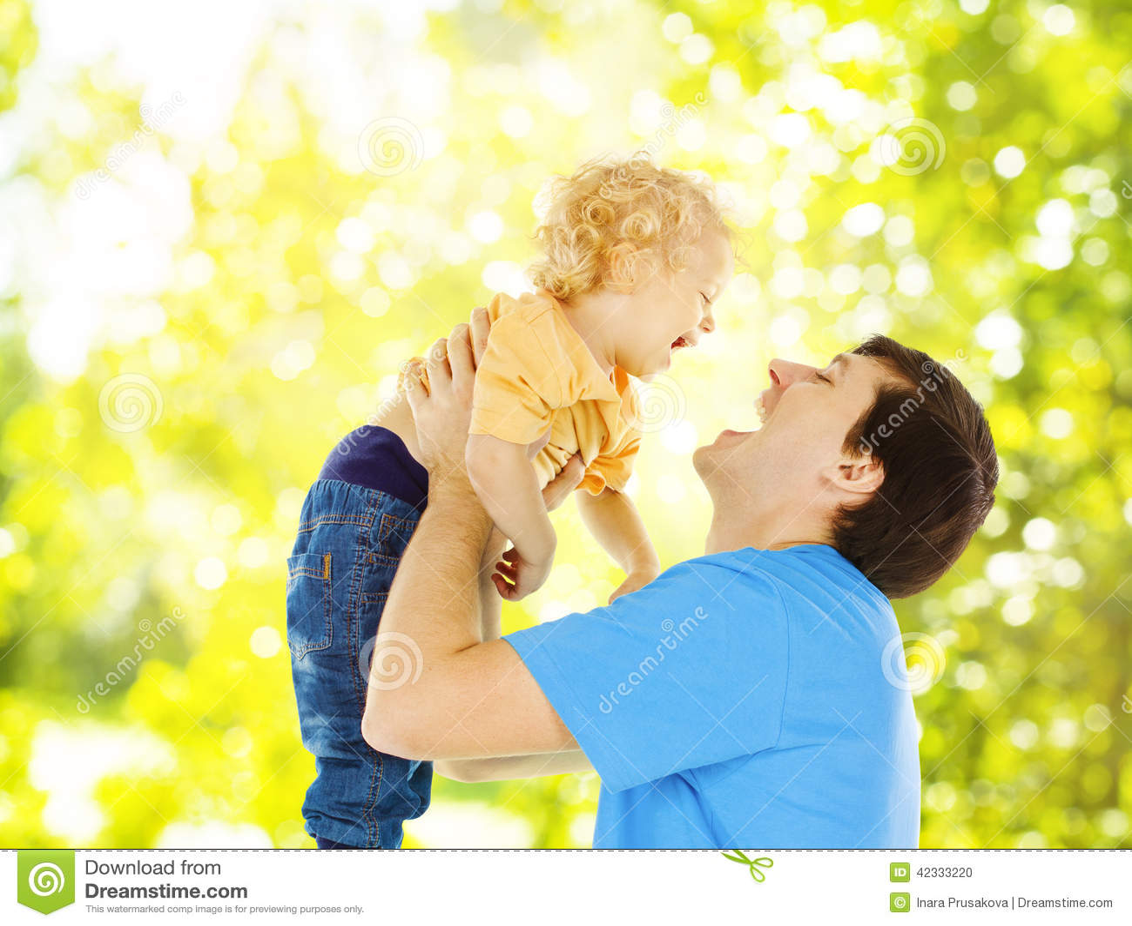 Vaderkind het gelukkige spelen De papa heft op glimlachende zoon over groen op