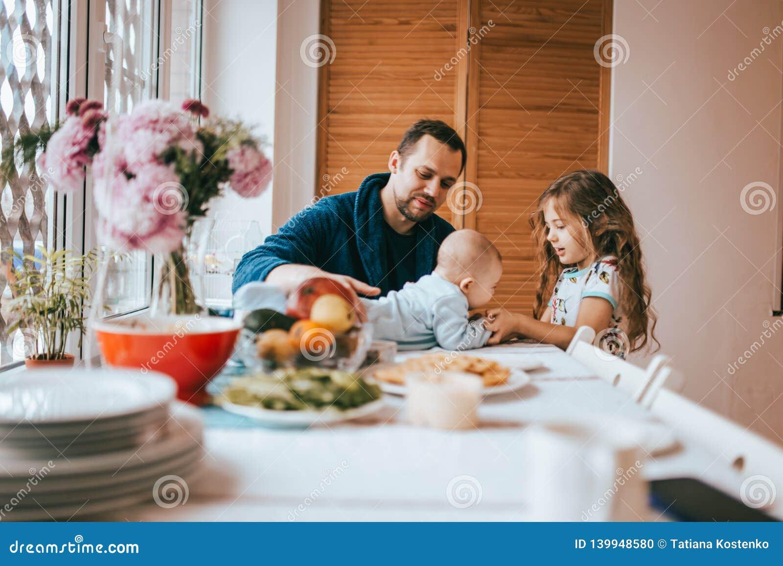 Vaderzitting op een stoel en en zijn kleine dochter die zich naast zijn blik bij de uiterst kleine baby bevinden die op de lijst