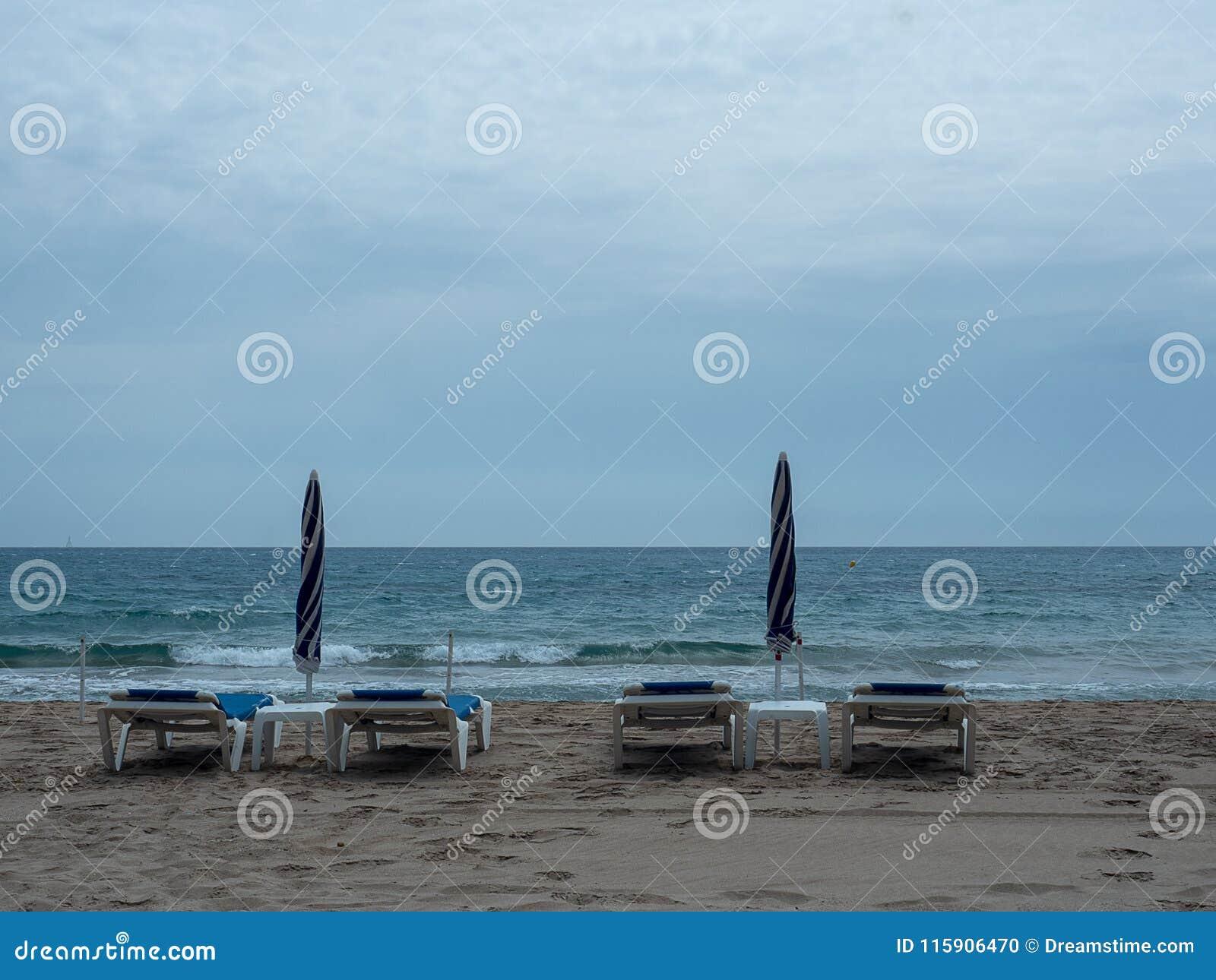 Vadios e guarda-chuvas de Sun fechados no litoral