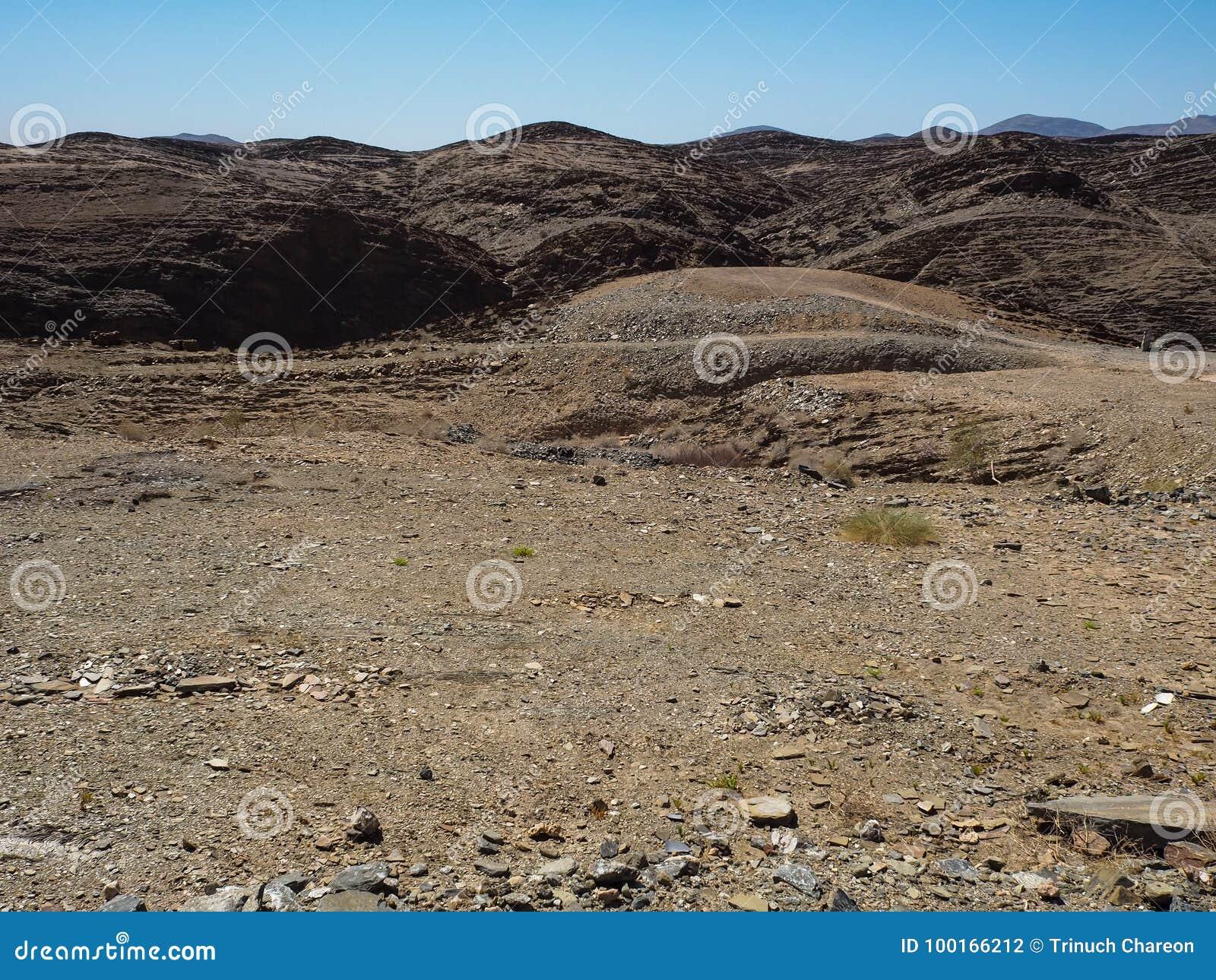 Vagga bakgrund för landskapet för bergtexturfoder av unik geografi för den Namib öknen med blixtrande stenjordning och ökenväxten