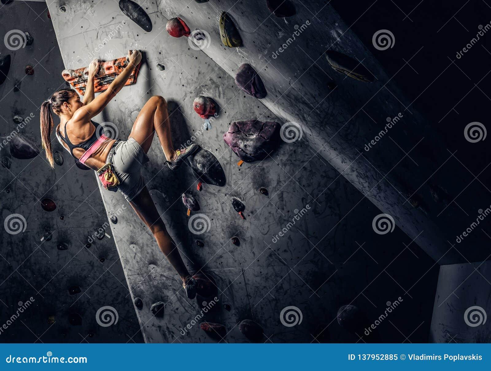 Vagga-klättring för sportswear för ung kvinna bärande övande på en vägg inomhus