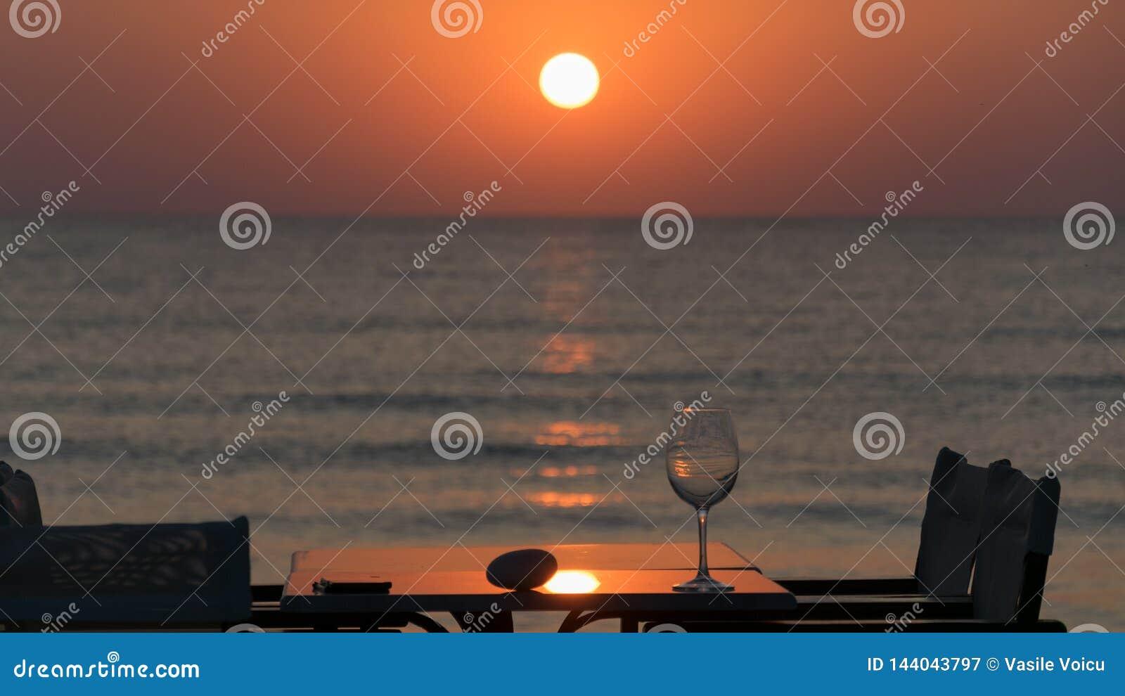 Vagga och exponeringsglas på en tabell med stolar och paraplyet i vass, på soluppgång på medelhavet