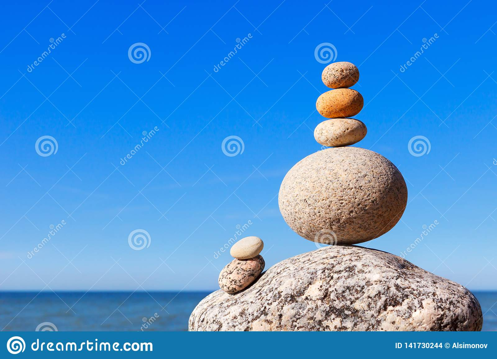 Vagga zenpyramiden av färgrika kiselstenar på en strand på bakgrunden av havet Begrepp av jämvikt, harmoni och meditationen