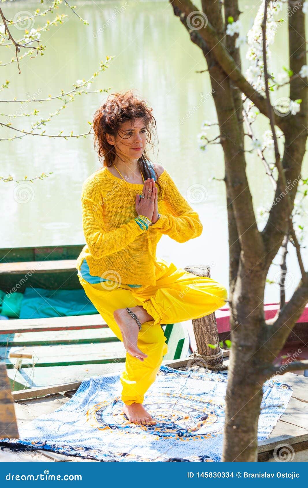 Vagos de la yoga de la práctica de la mujer joven el tiro lleno del cuerpo de la actitud de la balanza del día soleado del lago